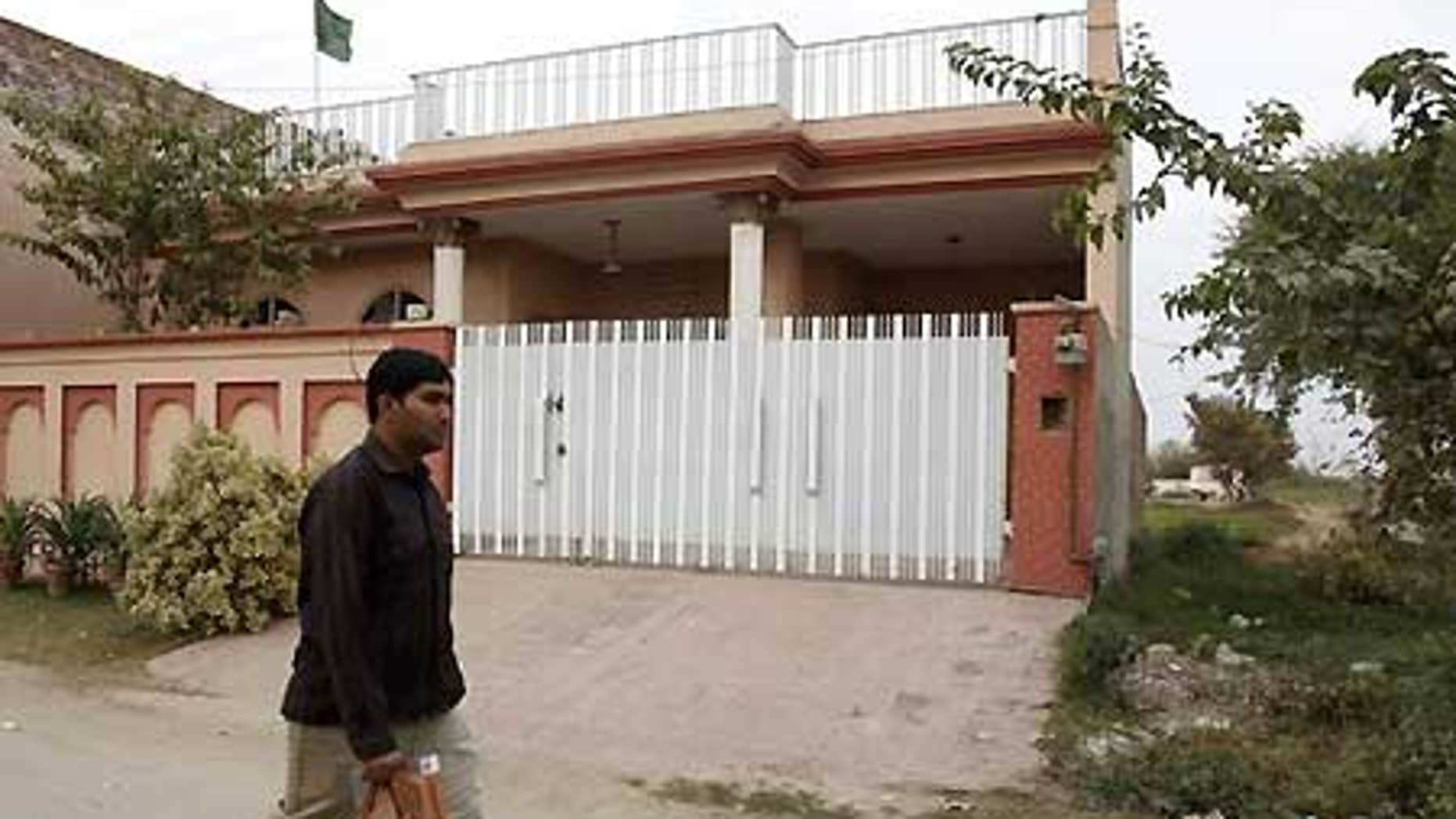 Dec. 10: A man walks past a house which residents say was raided by Pakistani security forces during the arrest of five Americans.