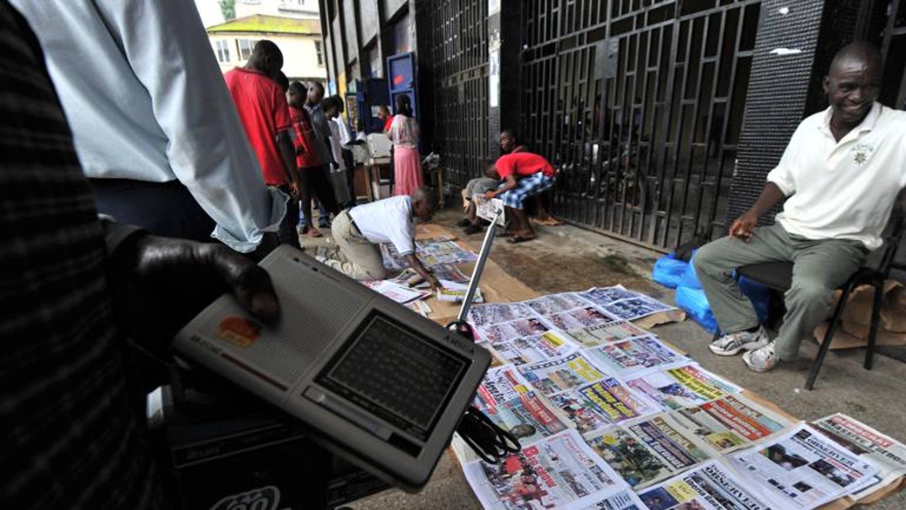 People look at newspaper headlines on a street in Monrovia on October 12, 2011
