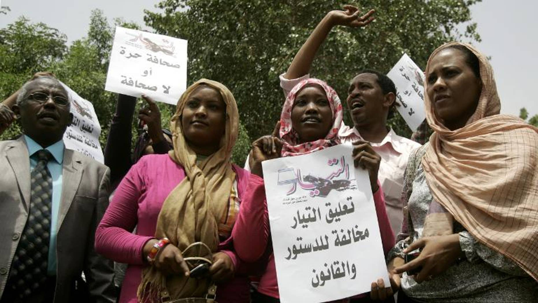 """Sudanese journalists hold slogans which read in Arabic """"Press freedom or no press"""" and """" Suspension of Al-Tayyar daily is against the constitution and law"""" in Khartoum on July 17, 2012"""