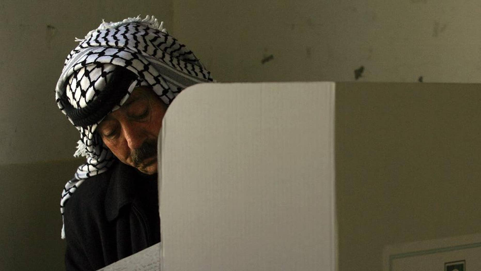 FILE - In this Jan. 22, 2006 file photo, a Palestinian police officer fills in his ballot before casting it in parliamentary elections in the West Bank city of Nablus. The Palestinian high court on Monday, Oct. 3, 2016 ruled upcoming municipal elections will be held in the West Bank only, excluding the Hamas-controlled Gaza Strip, in a move that suspends the first political contest in a decade between the rival Fatah and Hamas in both territories. (AP Photo/Emilio Morenatti, File)