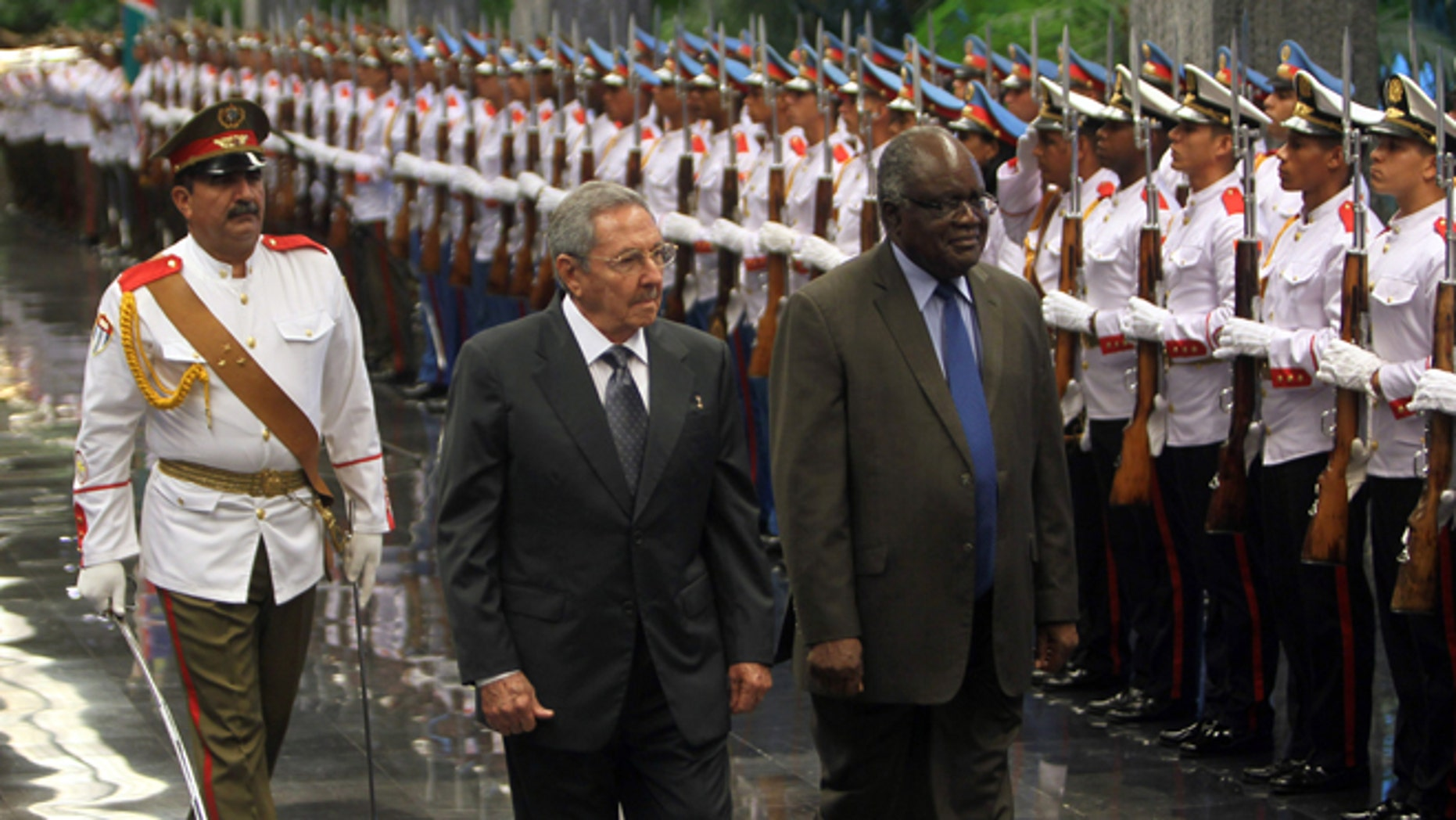 Cuba's President Raul Castro, center, and Namibia's President Hifikepunye Pohamba, right, review an honor guard in Havana, Cuba, Monday, Sept 29, 2014. Pohamba is on a three-day official visit to Cuba. (AP Photo/Ismael Francisco, Cubadebate)