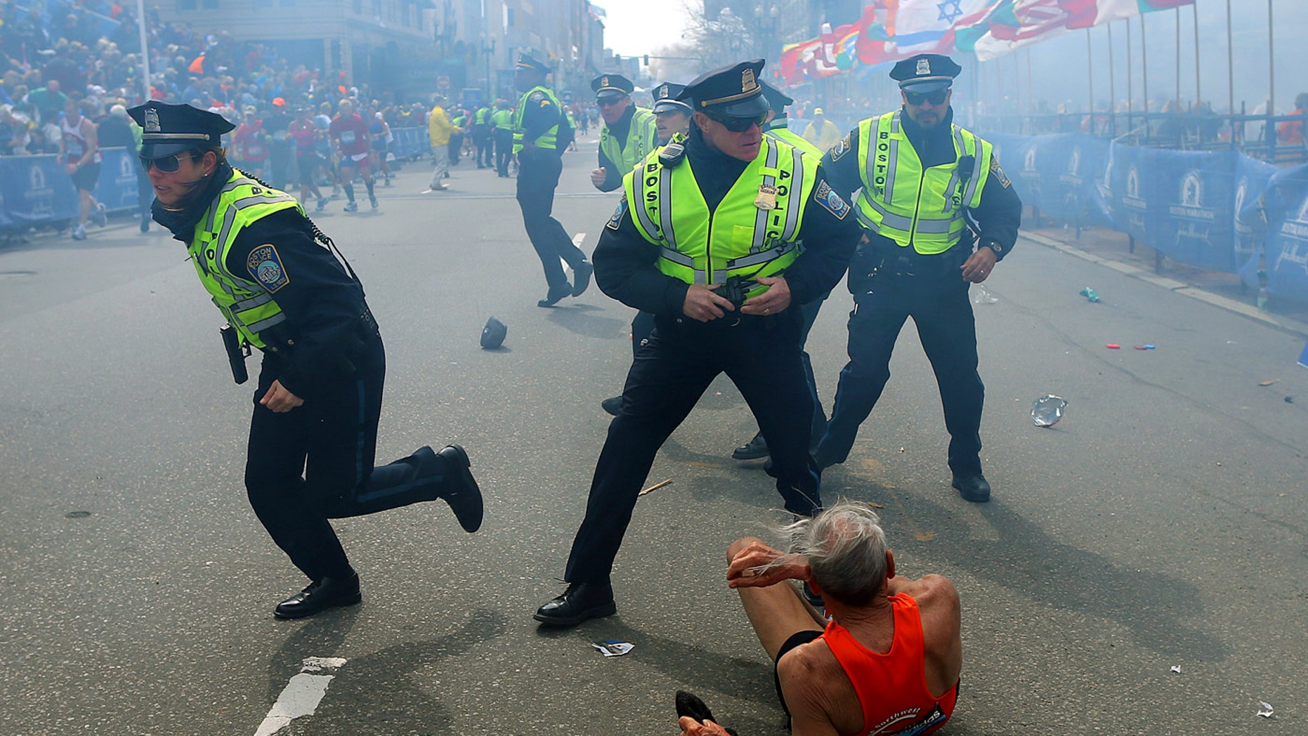 Police officers react to a second explosion at the finish line of the Boston Marathon in Boston, Monday, April 15, 2013. Two explosions shattered the euphoria of the Boston Marathon finish line on Monday, sending authorities out on the course to carry off the injured while the stragglers were rerouted away from the smoking site of the blasts. (AP Photo/The Boston Globe,  John Tlumacki)
