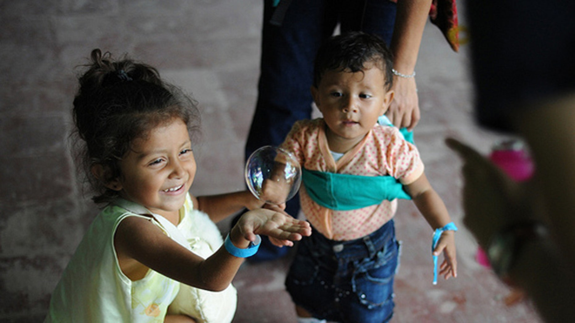 Children chase bubbles outside the family medicine exam room during a Continuing Promise 2011 medical community service event Las Morenas medical site in Puerto San José, Guatemala. (U.S. Navy photo by Mass Communication Specialist 2nd Class Eric C. Tretter/Released)
