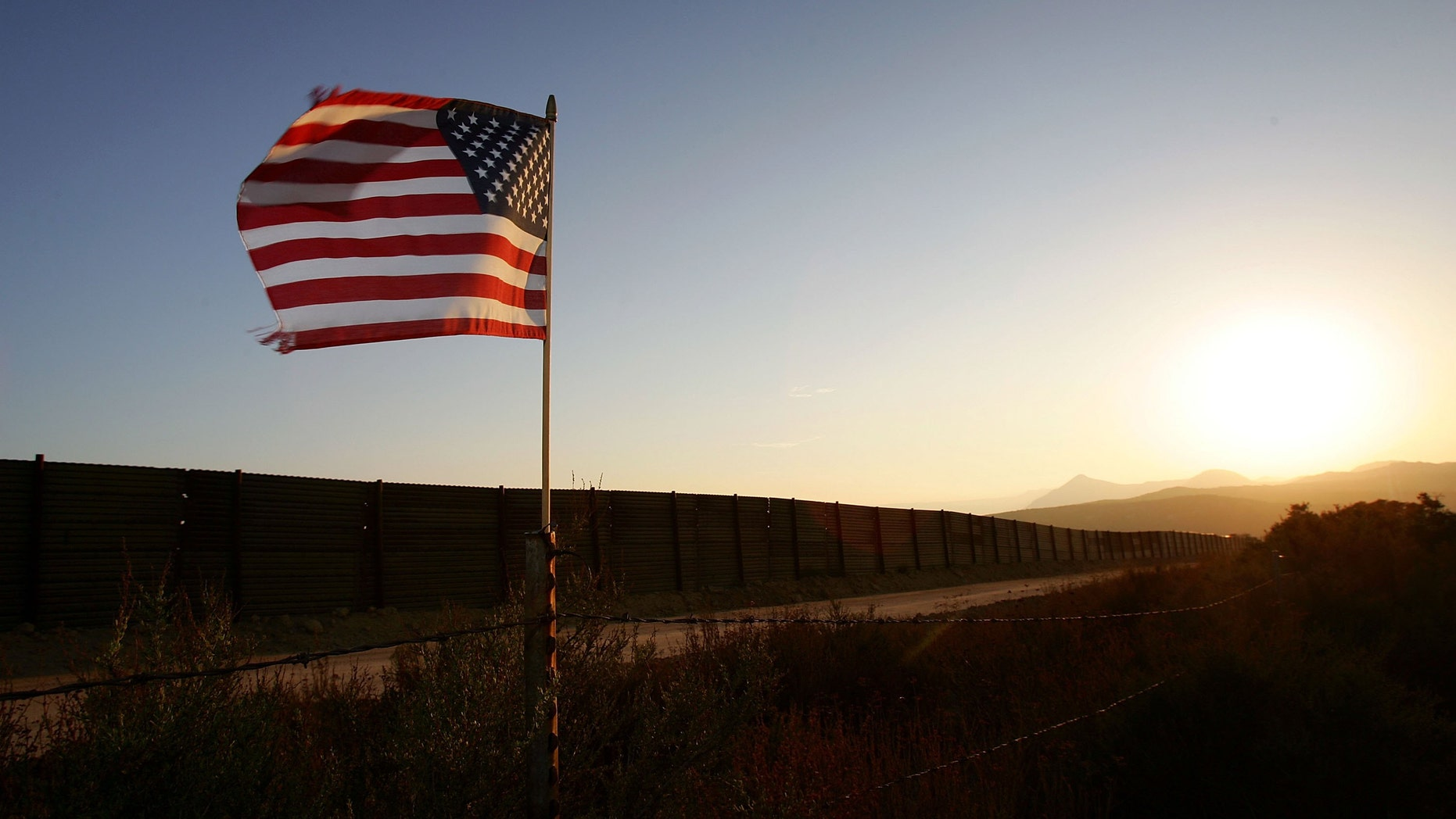 CAMPO, CA - OCTOBER 08:  A U.S. flag put up by activists who oppose illegal immigration flies near the US-Mexico border fence in an area where they search for border crossers October 8, 2006 near Campo, California. The activists want the fence expanded into a fully-lit double-fenced barrier between the US (foreground) and Mexico. US Fish and Wildlife Service wardens and environmentalists warn that a proposed plan by US lawmakers to construct 700 miles of double fencing along the 2,000-mile US-Mexico border, in an attempt to wall-out illegal immigrants, would also harm rare wildlife. Wildlife experts say cactus-pollinating insects would fly around fence lights, birds that migrate by starlight in the desert wilderness would be confused, and large mammals such as jaguars, Mexican wolves, Sonoran pronghorn antelope, and desert bighorn sheep would be blocked from migrating across the international border, from California to Texas.  (Photo by David McNew/Getty Images)