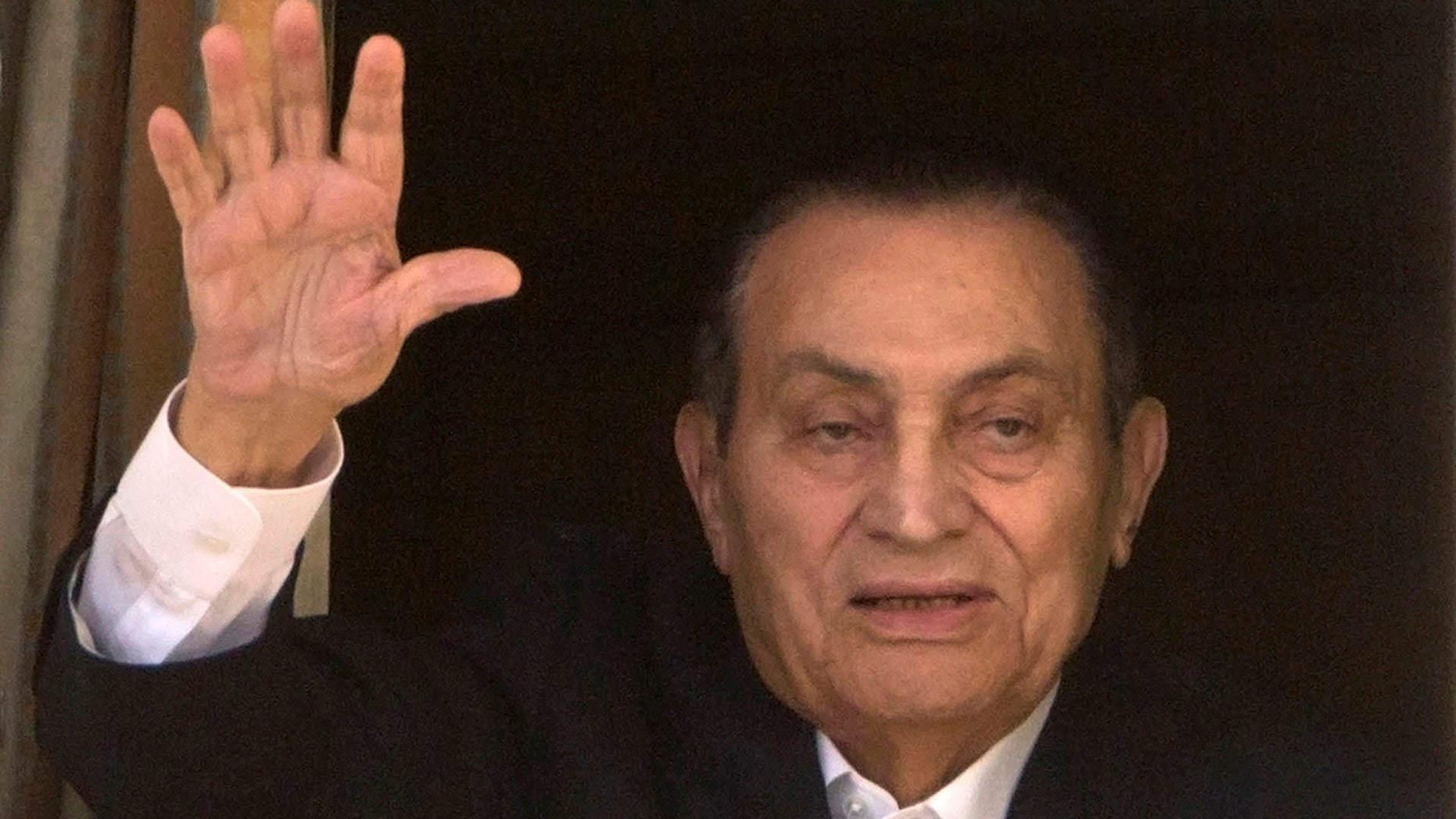 In this April 25, 2016 file photo, ousted Egyptian President Hosni Mubarak waves to his supporters from his room at the Maadi Military Hospital, where he is hospitalized, as they celebrate Sinai Liberation Day that marks the final withdrawal of all Israeli military forces from Egypt's Sinai Peninsula in 1982, in Cairo, Egypt.
