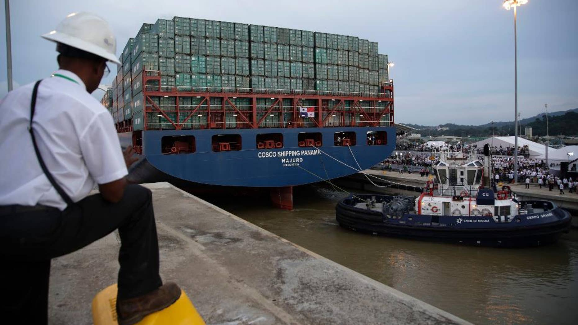 FILE - In this June 26, 2016, file photo, a worker watches as the COSCO Shipping Panama cargo ship leaves the new Cocoli Locks, part of the new Panama Canal expansion project, in Panama City. Canal administrator Jorge Quijano said Tuesday, July 26, that a Chinese container ship brushed with the canal's new wider locks due to bad weather and the ship not lining up correctly. (AP Photo/Tito Herrera, File)
