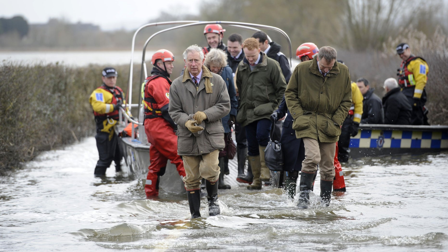Britain's Prince Charles, centre, walks through flood water after travelling to the flood-hit community of Muchleney and meeting with a local farming family at Thorney Moor Farm, to see the damage caused by the flood waters, Somerset, England, Tuesday, Feb. 4, 2014. (AP Photo/PA, Ben Birchall) UNITED KINGDOM OUT, NO SALES, NO ARCHIVE