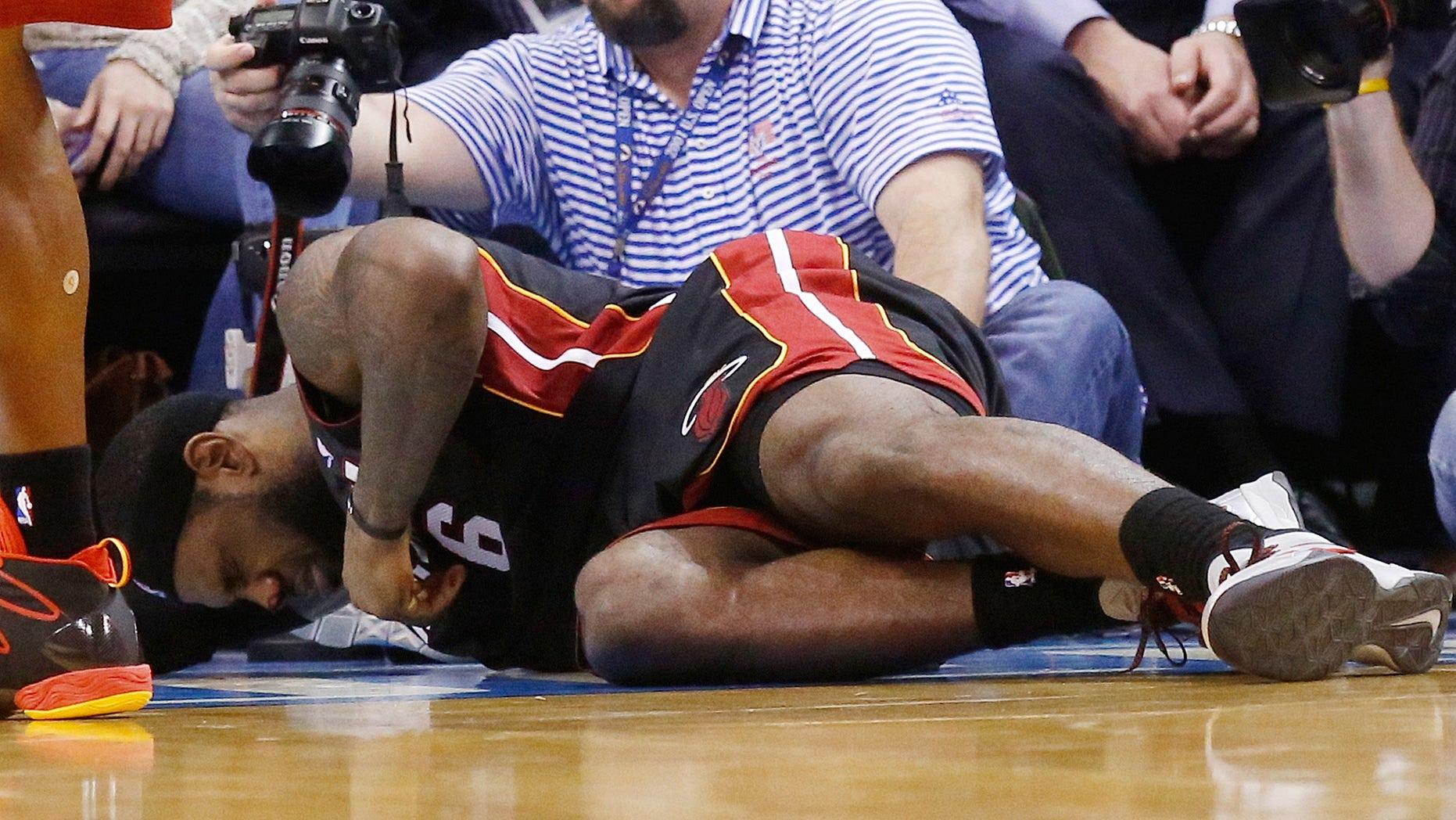 LeBron James, del Heat de Miami, se duele tendido en la duela tras ser impactado por Serge Ibaka en el cuarto periodo del duelo de la NBA frente al Thunder de Oklahoma City, el jueves 20 de febrero de 2014. James recibió el golpe mientras se enfilaba a la canasta. Completó una clavada, pero se fracturó la nariz en la jugada. (Foto AP/Sue Ogrocki)