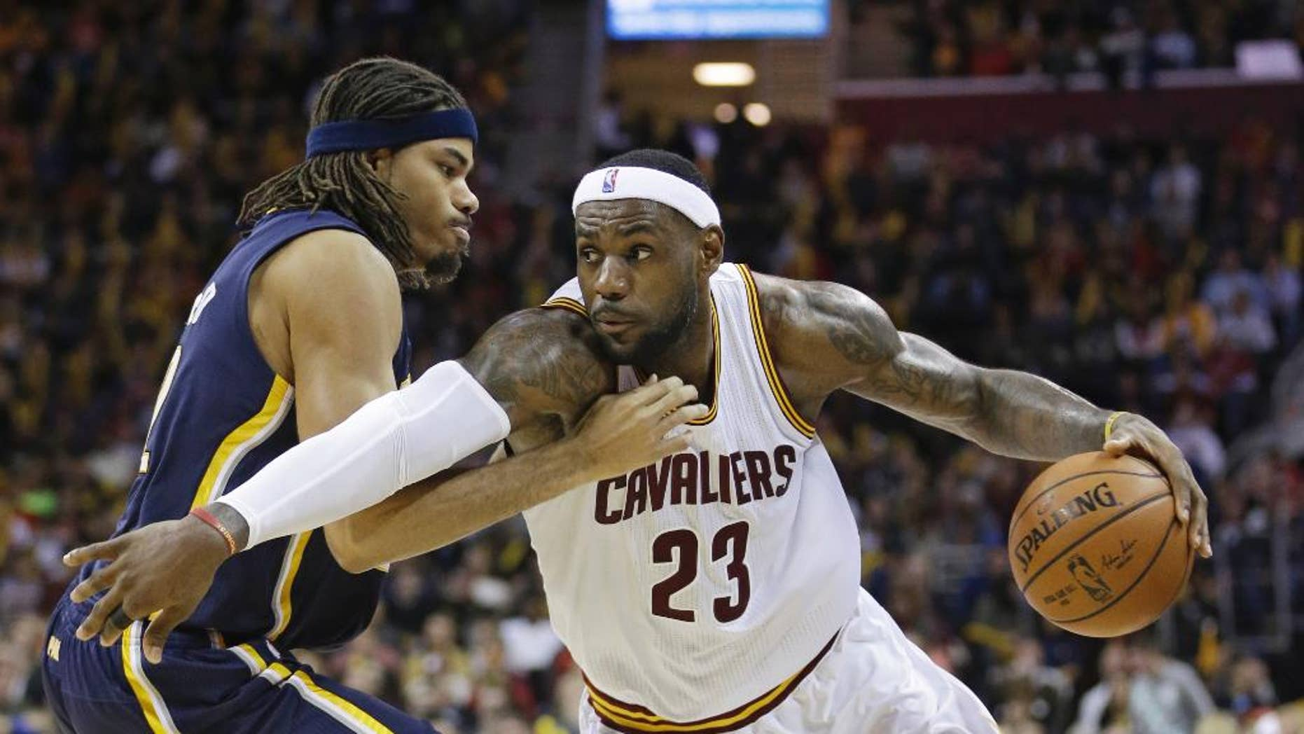 Cleveland Cavaliers' LeBron James, right, drives past Indiana Pacers' Chris Copeland  during the third quarter of an NBA basketball game Saturday, Nov. 29, 2014, in Cleveland. The Cavaliers defeated the Pacers 109-97. (AP Photo/Tony Dejak)