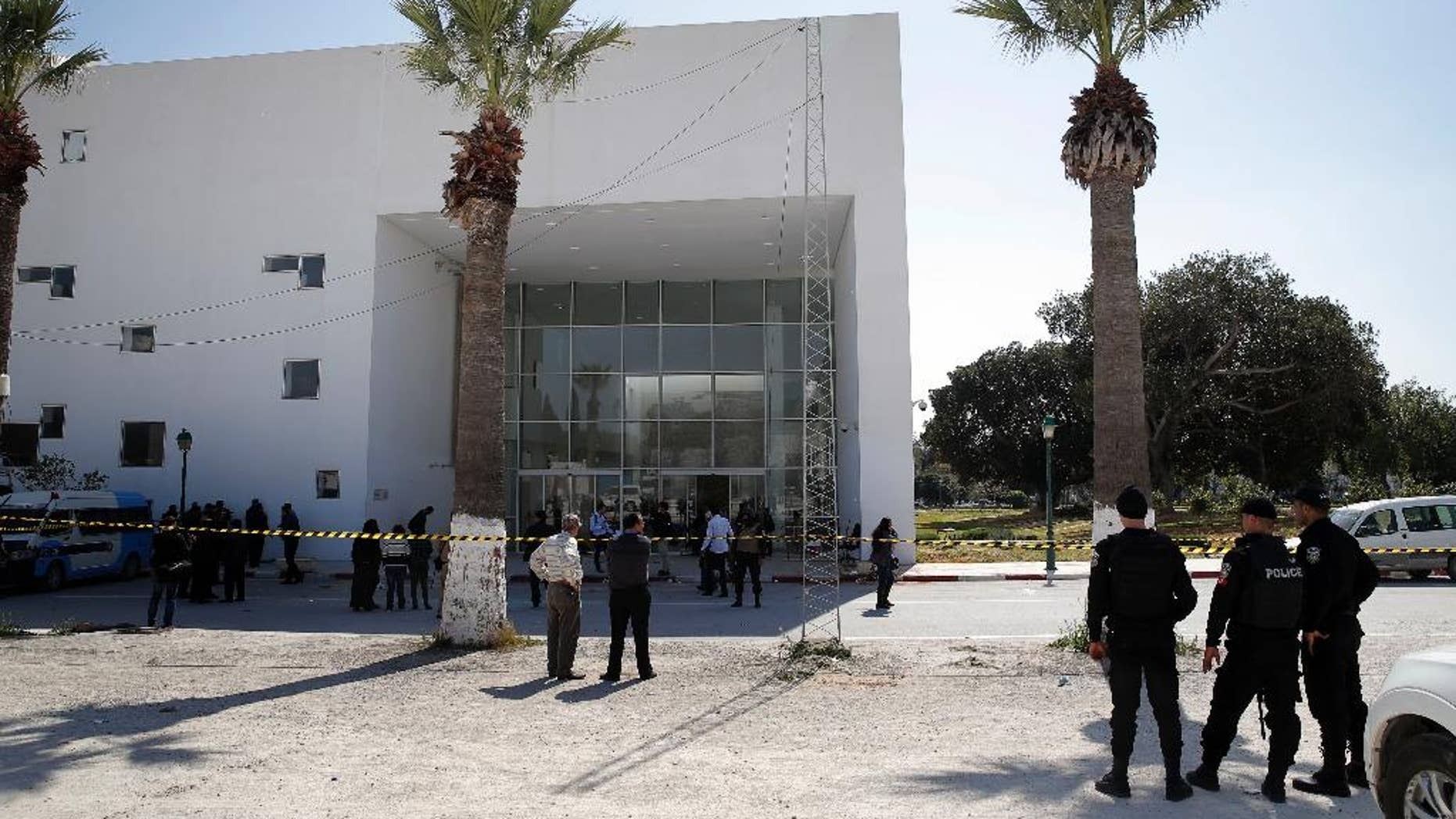 Policemen guard the entrance of the Bardo museum in Tunis, Tunisia, Thursday, March 19, 2015,  a day after gunmen opened fire killing over 20 people, mainly tourists. One of the two gunmen who killed  tourists and others at a prominent Tunisian museum was known to intelligence services, Tunisia's prime minister said Thursday. But no formal links to a particular terrorist group have been established in an attack that threatens the country's fledgling democracy and struggling tourism industry. (AP Photo/Christophe Ena)