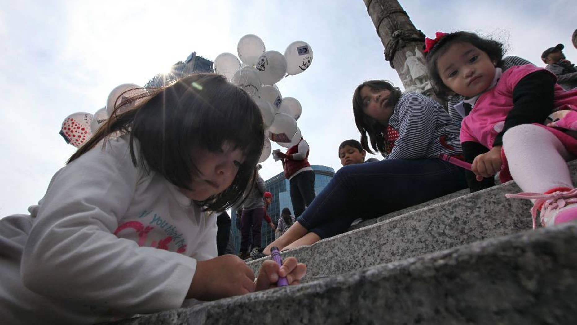 Children write letters for the feast of the Three Kings, asking for the 43 missing colleges students, in Mexico City, Sunday Jan. 4, 2015. The children along with their parents sent letters asking for the well being of the students that went missing after a clash with the local police of the town of Iguala on Southern Guerrero state, on Sept. 26, 2014. (AP Photo/Marco Ugarte)