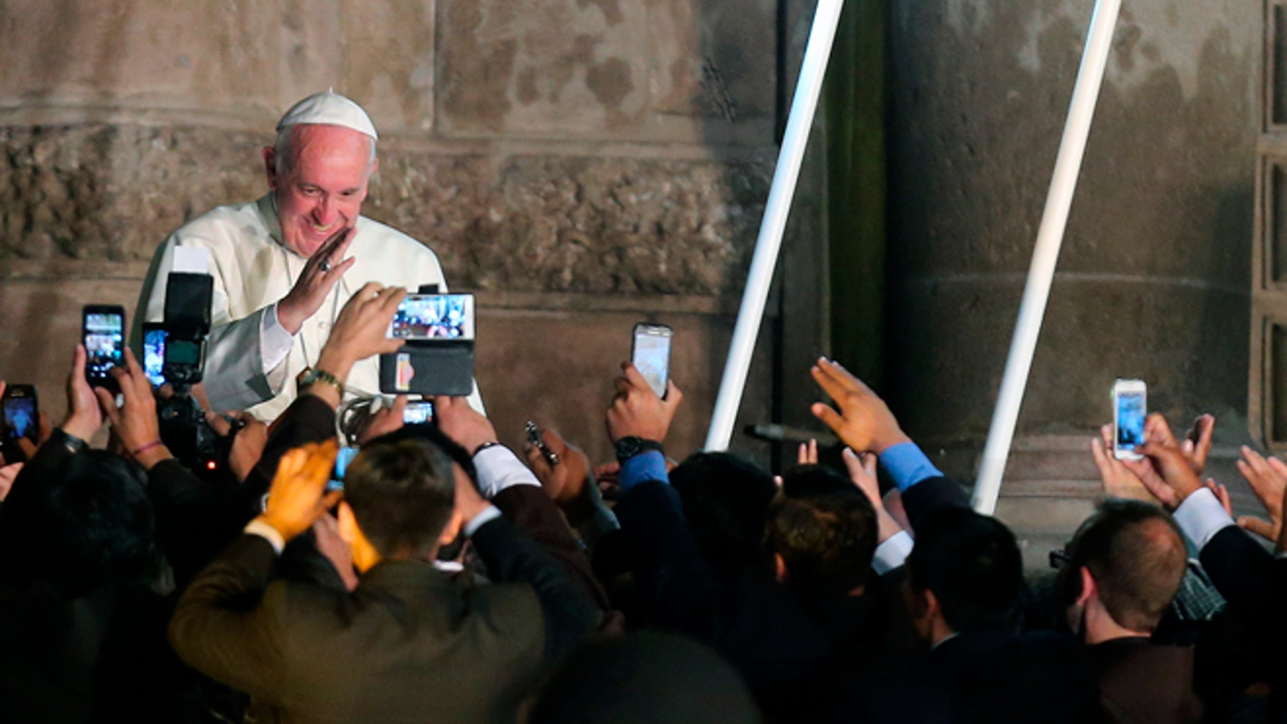 Faithful take picture with their mobile phones as Pope Francis departs from the San Francisco Church aboard the Popemobile, in Quito, Ecuador, Tuesday, July 7, 2015. The Pontiff met with representatives of civic organizations, entrepreneurs, indigenous communities and Catholic lay groups. (AP Photo/Fernando Llano)