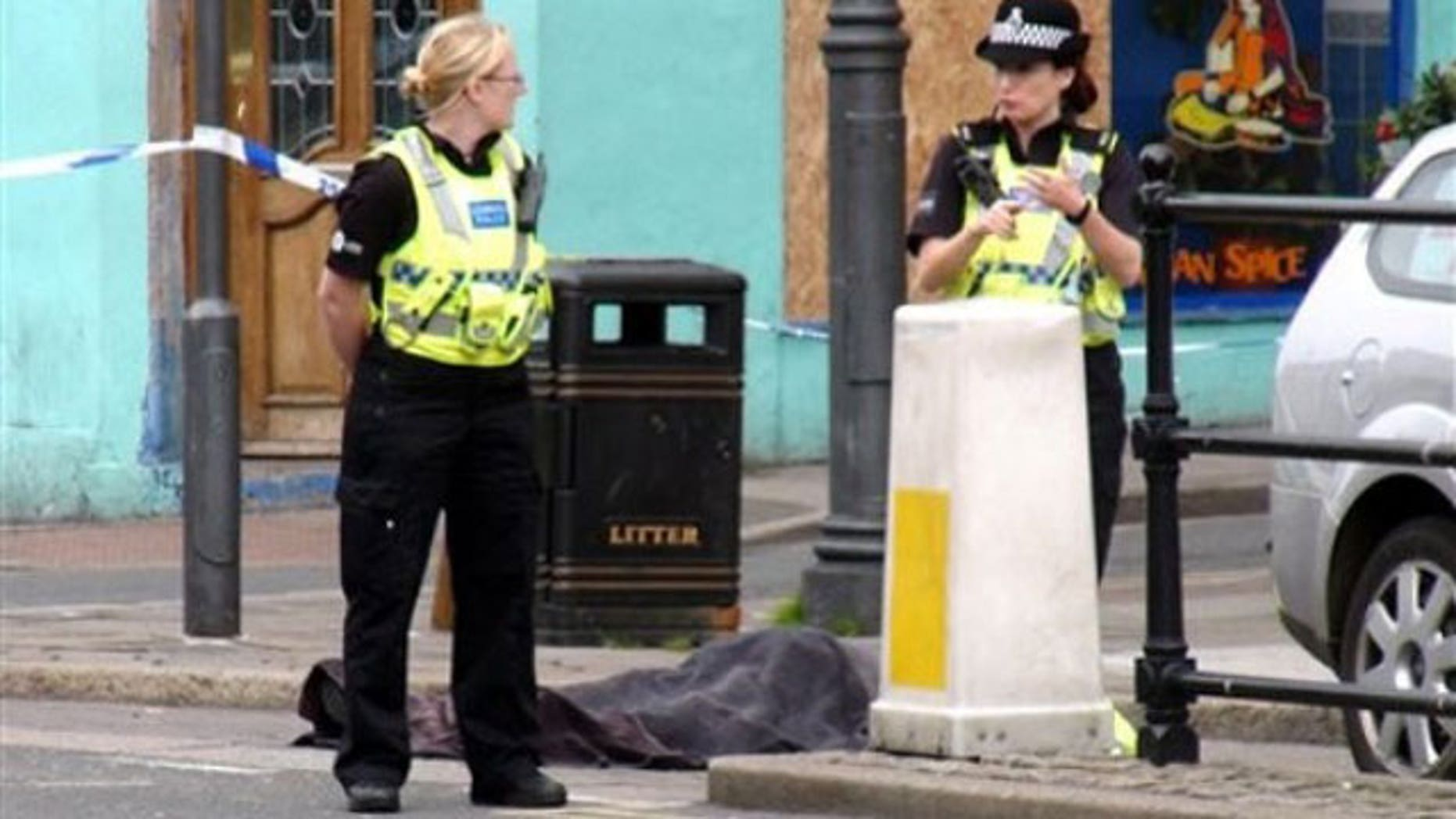 """June 2: Police stand next to a body following a shooting on Duke Street, in the town of Whitehaven in northwest England. British police were hunting down a man suspected in a shooting spree that has left more than one person dead in northwest England. The Cumbria Constabulary said there have been """"a number of fatalities"""" as well as several injuries after shots were fired in the town of Whitehaven and nearby Seascale and Egremont (AP)."""