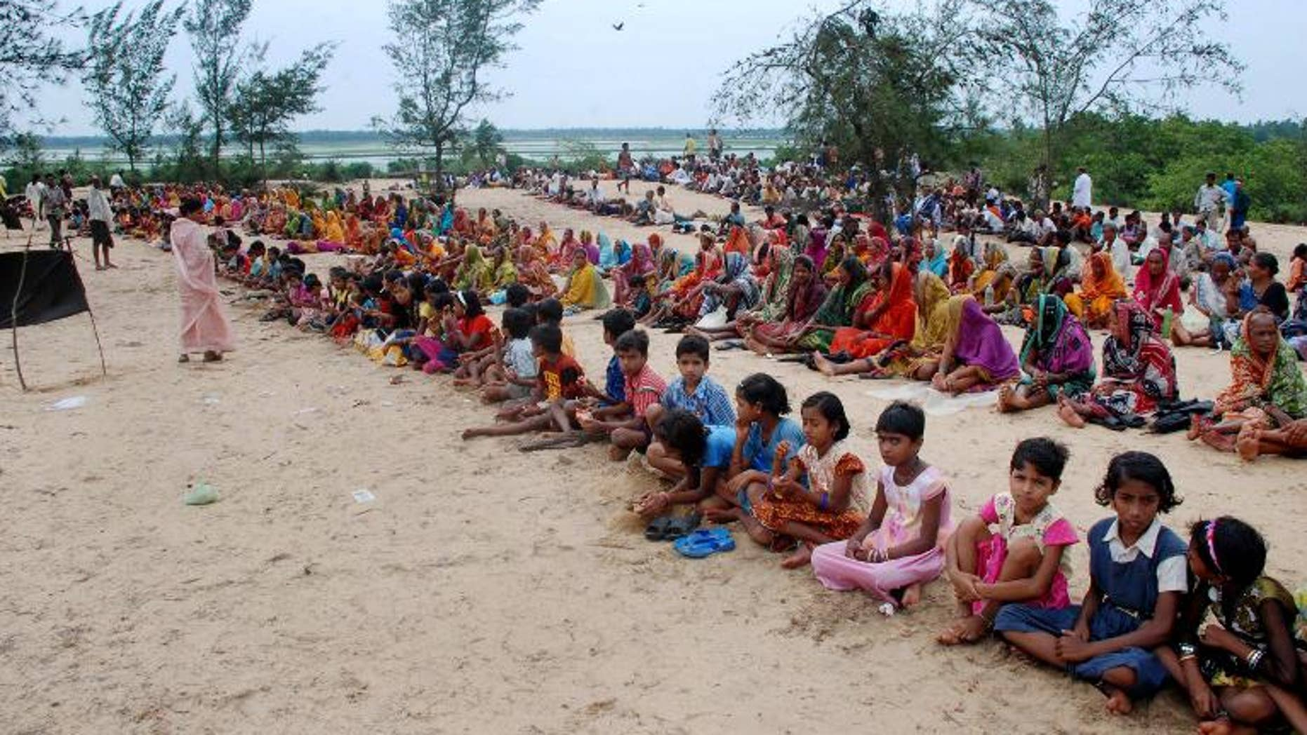 Villagers sit along the entry point to prevent policemen and officials from entering their land in Jagatsinghpur district, about 140 kilometres east of the eastern Indian city of Bhubaneswar, on June 18, 2011