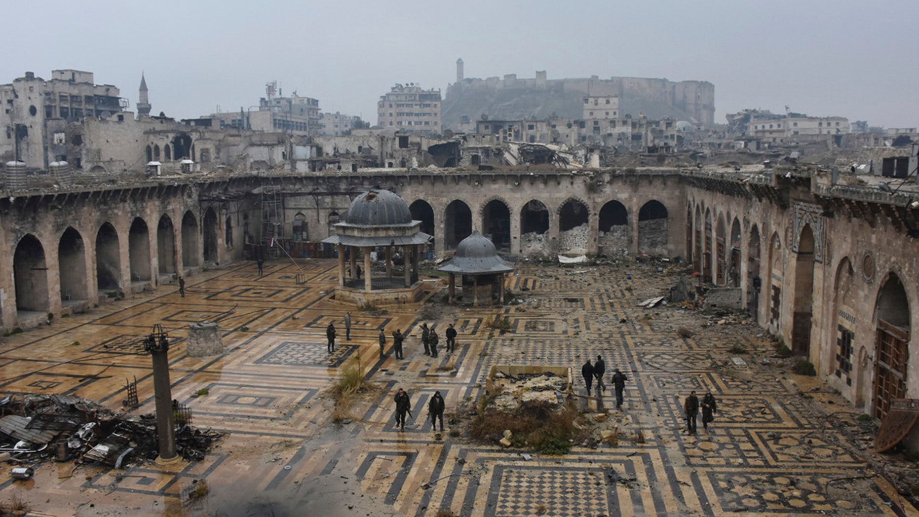 This photo released by the Syrian official news agency SANA, shows Syrian troops and pro-government gunmen marching walk inside the destroyed Grand Umayyad mosque in the old city of Aleppo, Syria, Tuesday, Dec. 13, 2016.