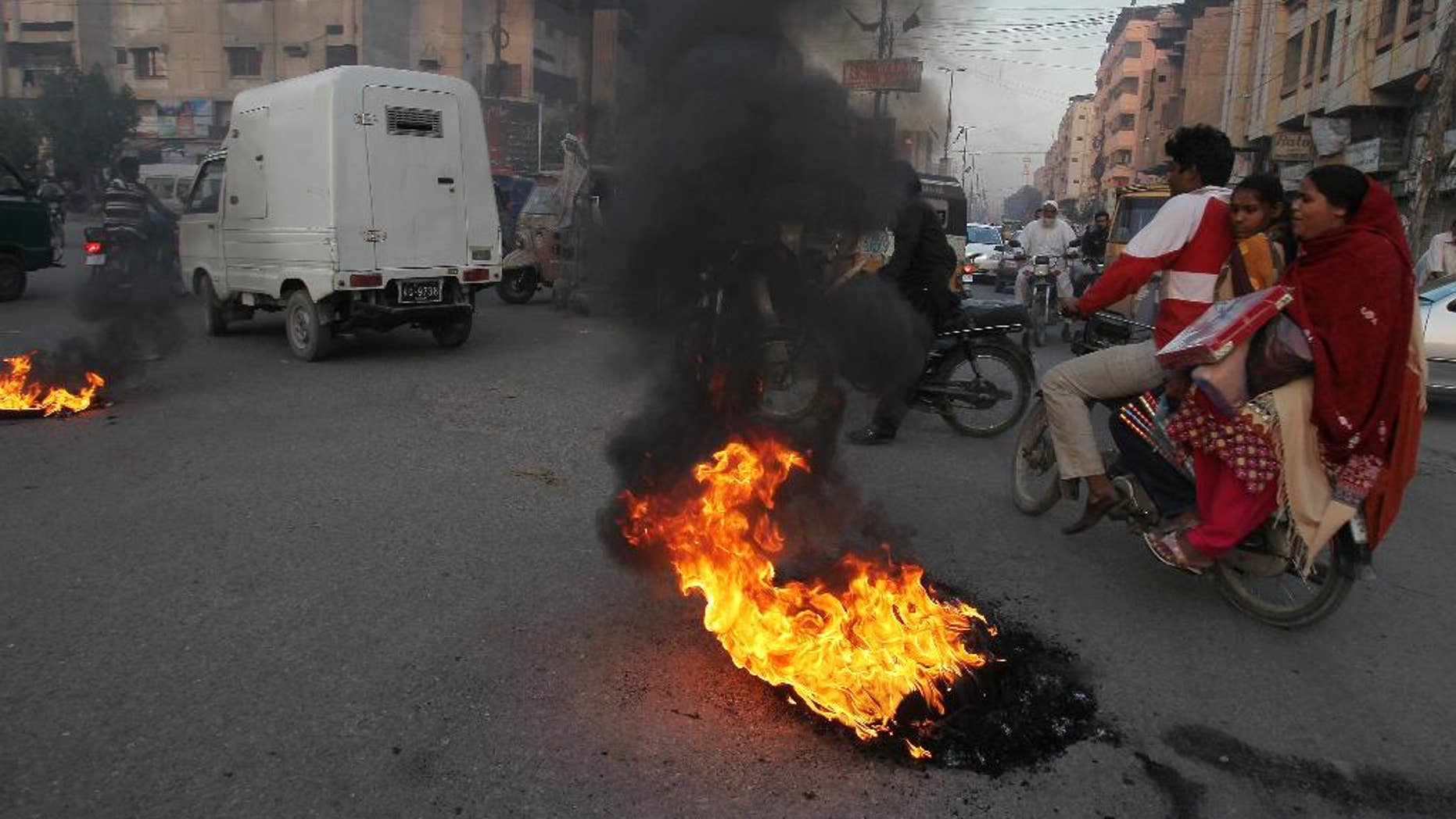 Pakistani protesters burn tires to condemn a blast at a Shiite mosque, Friday, Jan. 30, 2015 in Karachi, Pakistan. The bomb ripped through a mosque in Pakistan belonging to members of the Shiite minority sect of Islam just as worshippers were gathering for Friday prayers, killing dozens of people and wounding many others, officials said. (AP Photo/Fareed Khan)