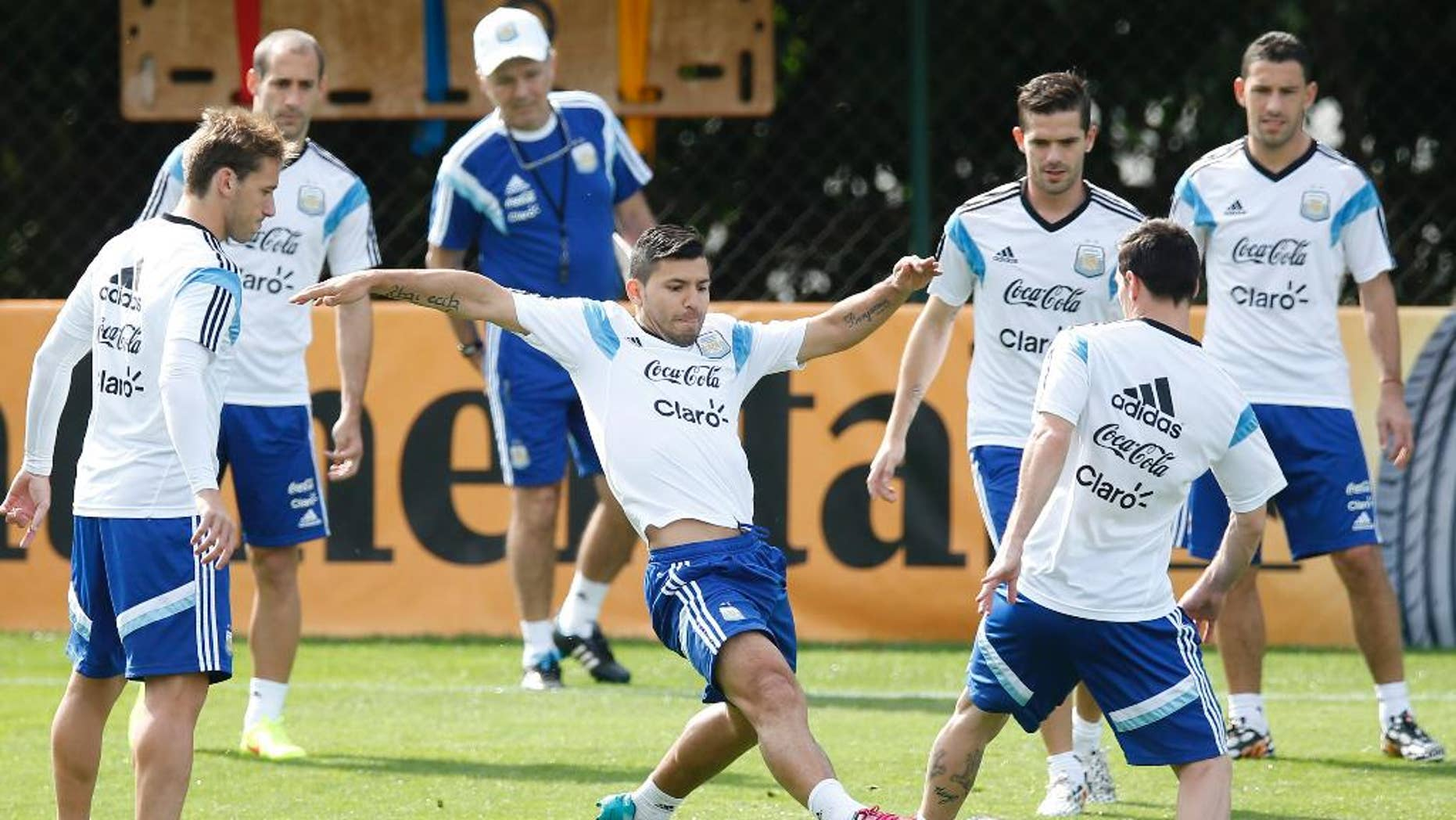 Argentina's Sergio Aguero, center, vies for the ball with Lionel Messi, right, during a training session in Vespasiano, near Belo Horizonte, Brazil, Wednesday, June 18, 2014.  Argentina plays in group F of the 2014 soccer World Cup. (AP Photo/Victor R. Caivano)