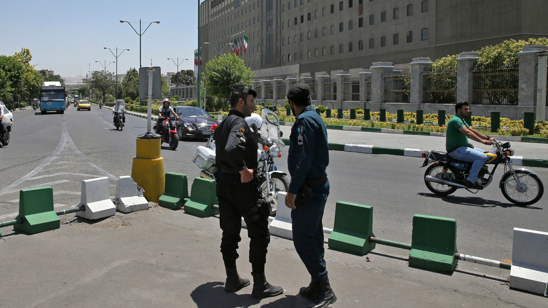 Police officers stand guard as vehicles drive past Iran's parliament building in Tehran, Iran, Thursday, May 8, 2017.