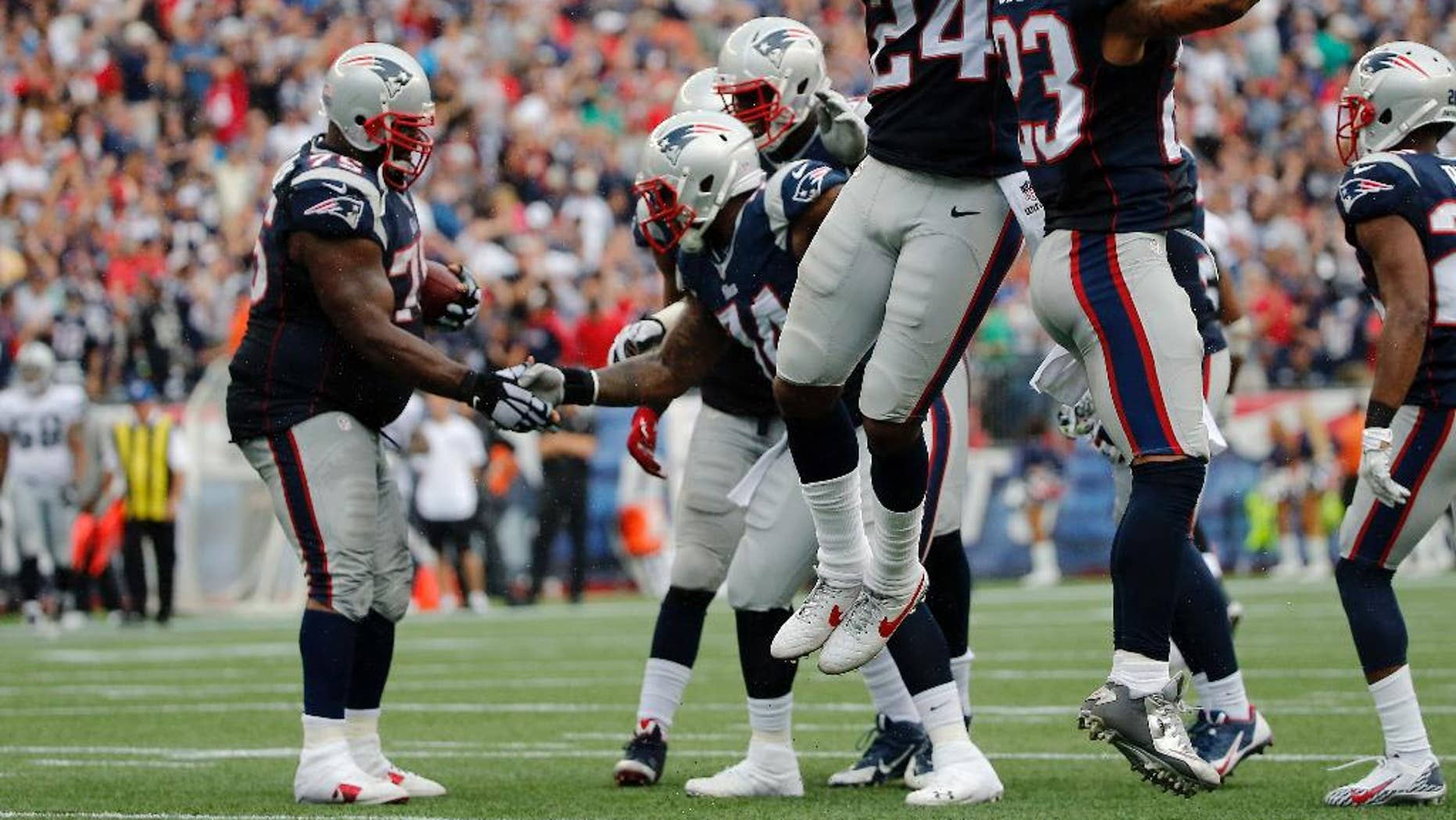 New England Patriots defensive backs Darrelle Revis (24) and Patrick Chung (23) celebrate an interception by Vince Wilfork, left, in the fourth quarter of an NFL football game against the Oakland Raiders, Sunday, Sept. 21, 2014, in Foxborough, Mass. The Patriots won 16-9. (AP Photo/Elise Amendola)