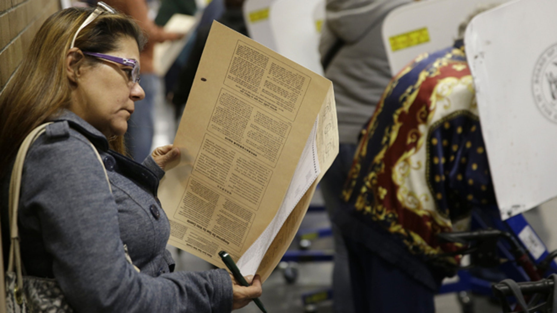 Because all the privacy booths are full, Miriam Rodriguez looks over her ballot while leaning against the wall at a polling site in New York, Tuesday, Nov. 4, 2014. (AP Photo/Seth Wenig)