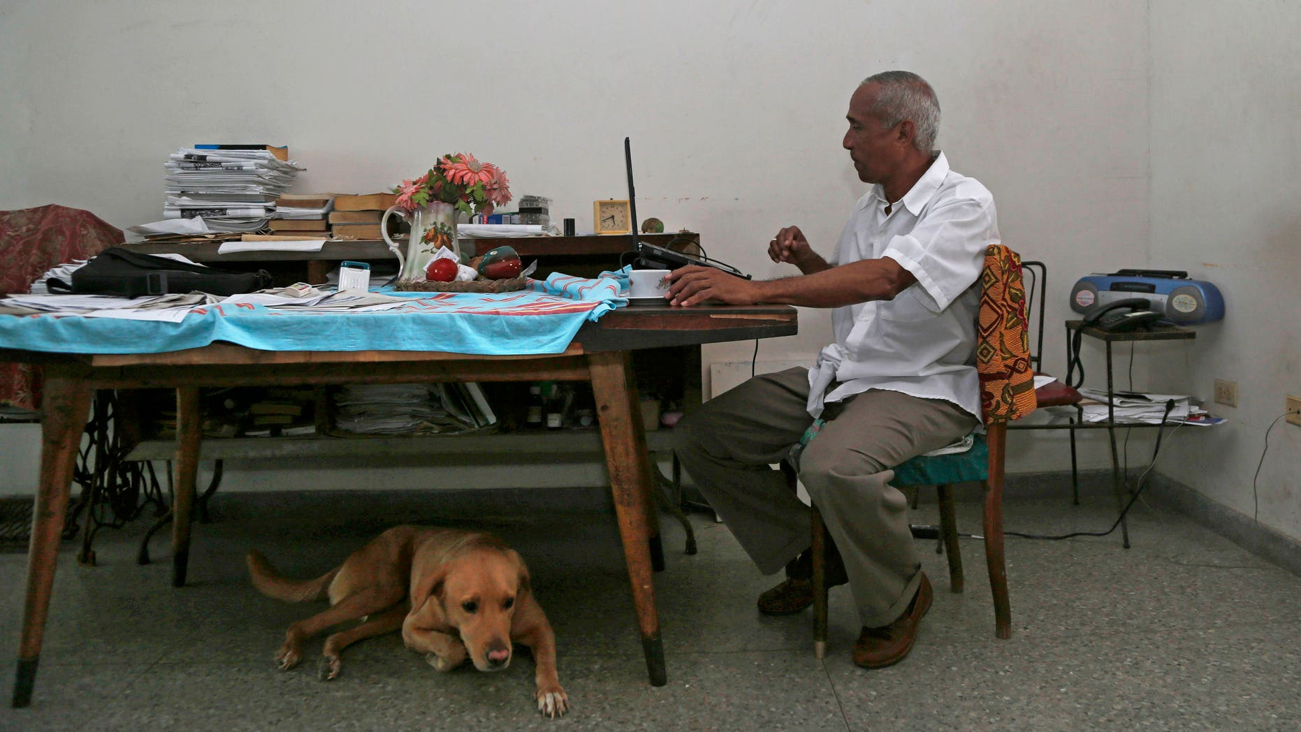 In this Thursday, April 16, 2015 photo, Cuban dissident Hildebrando Chaviano works at his laptop inside his home in Havana, Cuba. Chaviano, a government lawyer turned independent journalist, is one of at least two Cuban dissidents who made it past a first round of voting to become candidates in Sunday's local elections. (AP Photo/Desmond Boylan)