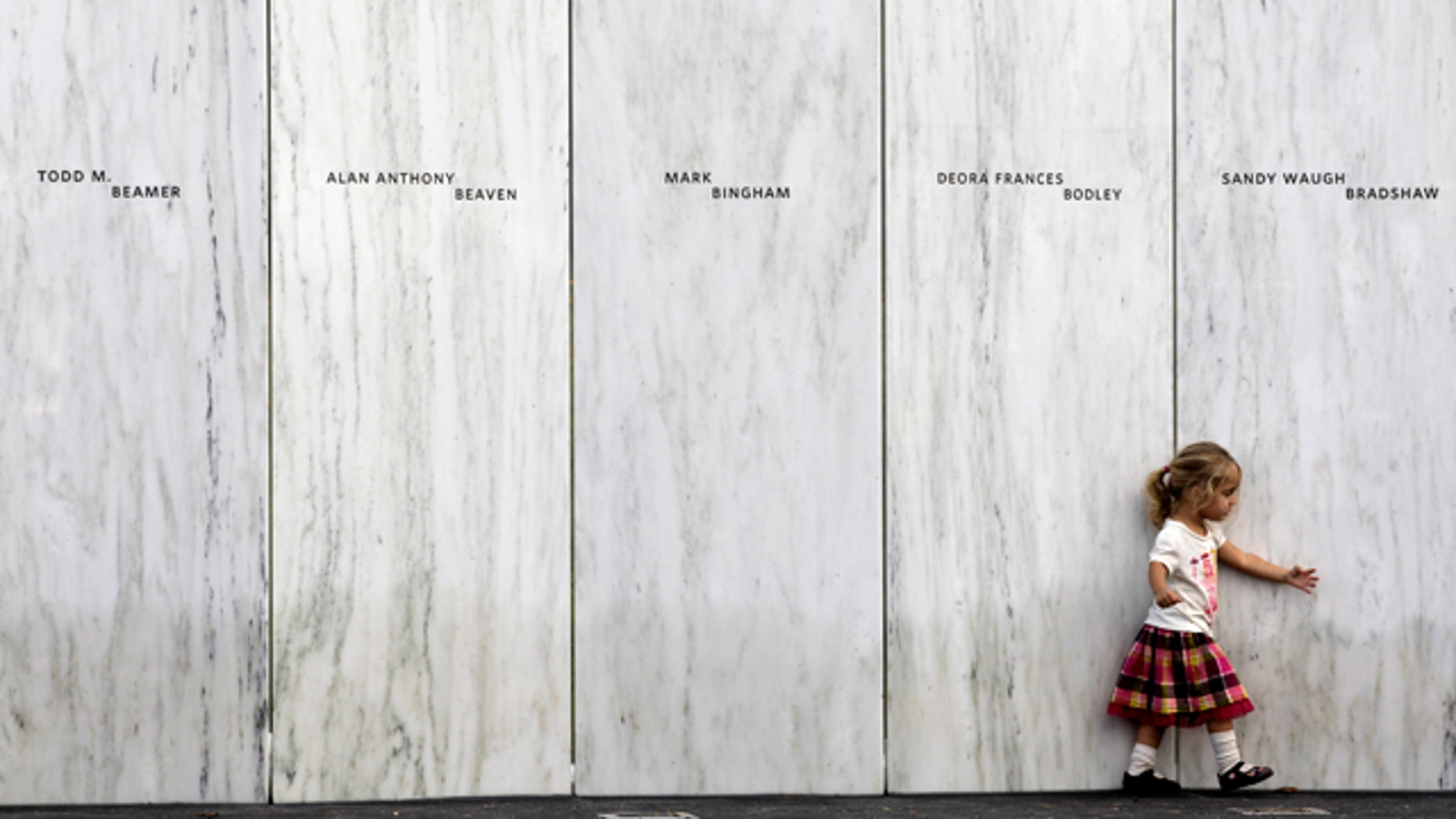 Sept 10: A family member of one of the victims of the crash of United Flight 93 walks along a section of Phase 1 of the permanent National Memorial following its dedication, near the crash site of Flight 93 in Shanksville, Pa.   The names of the 40 victims of the crash are iny Sanscribed on the marble panels.
