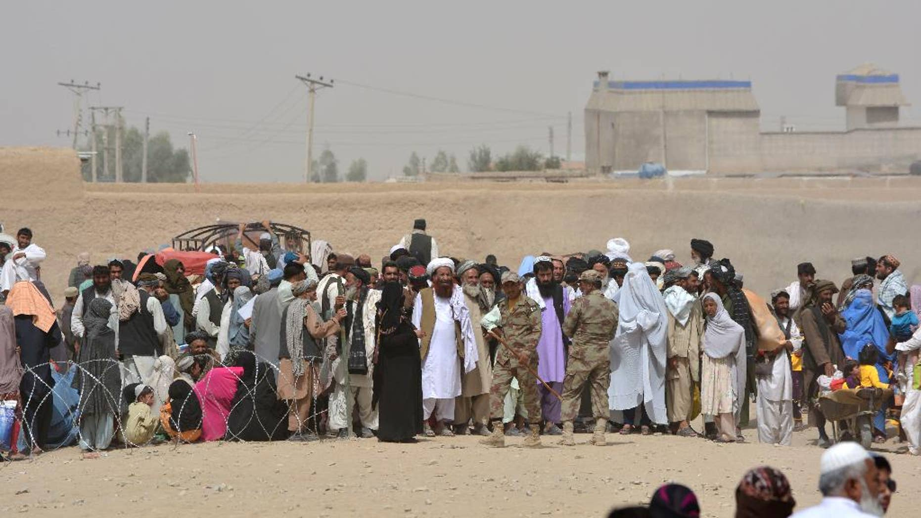 People en route to Afghanistan wait at the Pakistani border post, Chaman, Wednesday, Aug. 31, 2016. Border crossing in Chaman in southwest Pakistan is closed for 15th consecutive day after Afghan protesters burned a Pakistani flag on the other side of the border. Border will reopen on Thursday morning after negotiations between Pak and Afghan officials, official said. (AP Photo/Matiullah Achakzai)