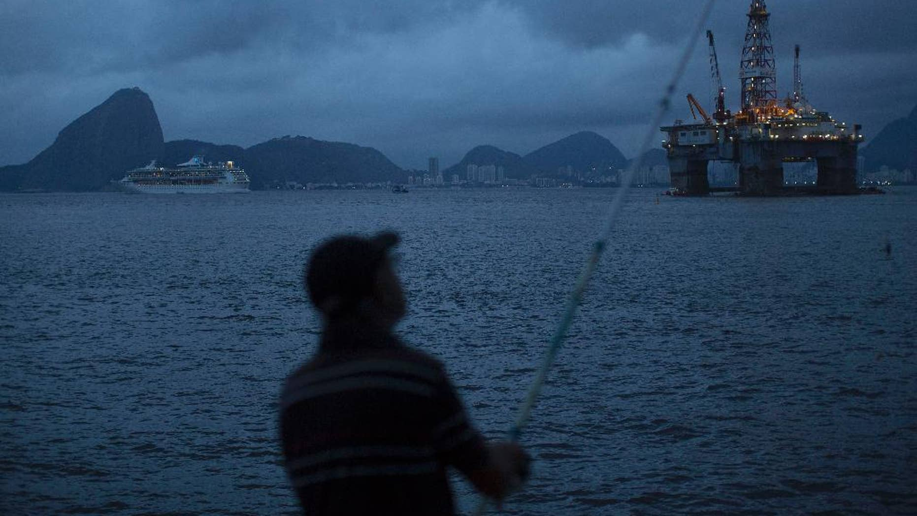 FILE - In this April 21, 2015 file photo, a man fishes in Guanabara Bay where an oil platform floats, backdropped by Sugar Loaf Mountain, left, in Niteroi, Brazil. The Brazilian government on Monday, Sept. 12, 2016 ratified its participation in the Paris Agreement on climate change, a significant step by Latin America's largest emitter of greenhouse gases that could spur other countries to move forward. (AP Photo/Leo Correa, File)