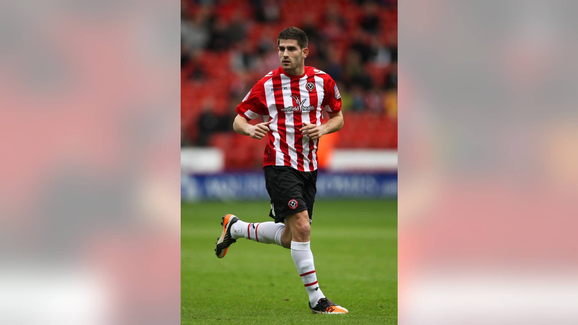 FILE - This March 17, 2013 file photo of footballer Ched Evans at Sheffield United. The former Premier League footballer who was convicted of rape has been told he can resume training with third tier club Sheffield United amid a national debate about the decision.  (AP Photo/Nick Potts, PA) UNITED KINGDOM OUT