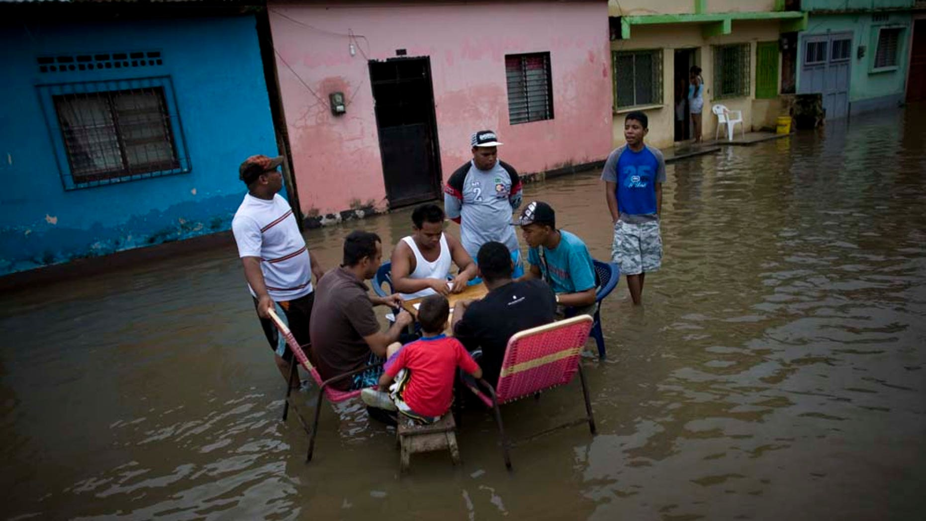 People play dominos in a flooded street in Higuerote, Venezuela, Tuesday Nov. 30, 2010.  Flooding and landslides unleashed by torrential rains have killed at least 30 people in Venezuela and forced thousands from their homes.  (AP Photo/Ariana Cubillos)