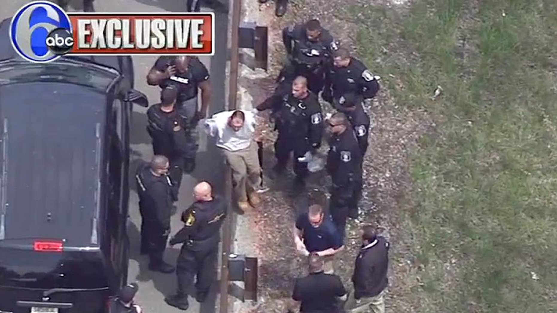 In this frame grab taken from video, Arthur Buckel, center, sits on a guardrail surrounded by police officers after being taken into custody near Double Trouble State Park, Monday, May 9, 2016, in Lacey Township, N.J. The minimum security prison inmate who escaped last week once served time for manslaughter for killing a baby and had been behind bars on assault, drug possession and burglary charges. (AP Photo/ WPVI-TV)