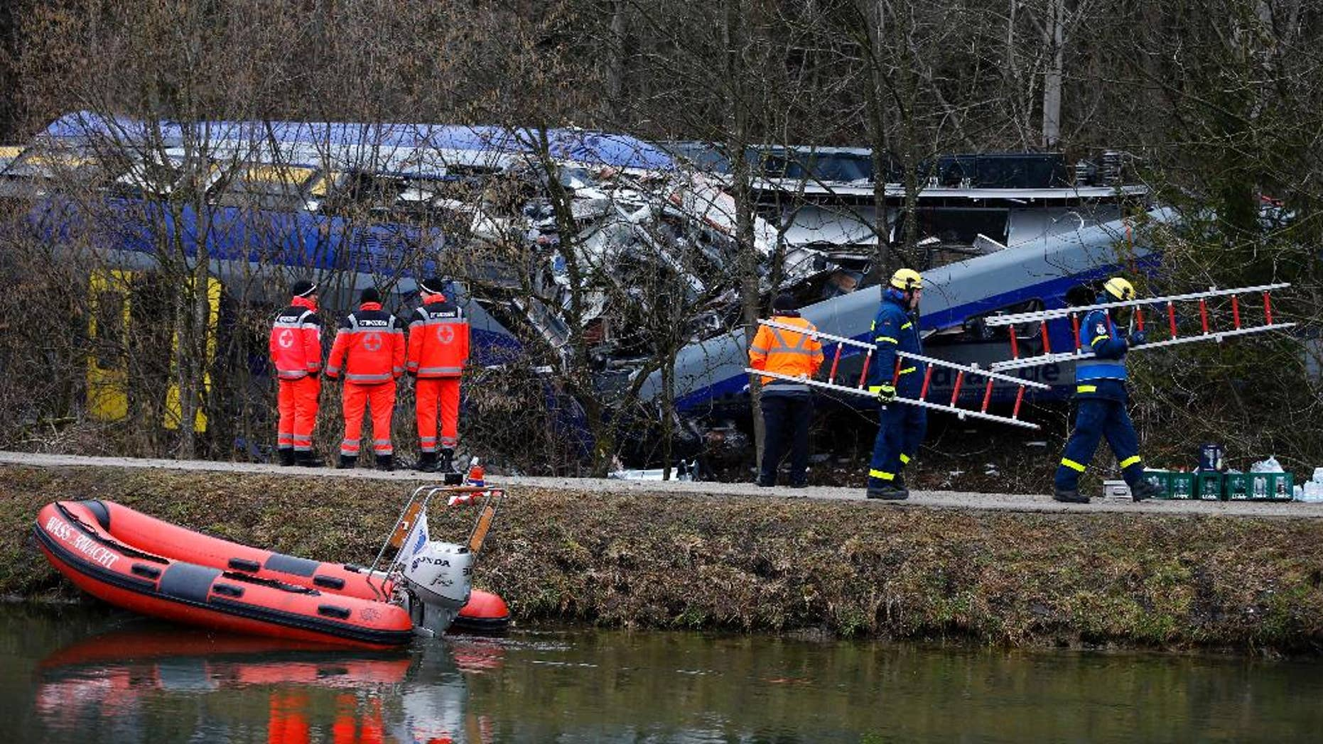 FILE - In this Feb. 10, 2016 file picture rescue personnel stand in front of trains that collided head-on near Bad Aibling, Germany.  Prosecutors are seeking a four-year jail sentence for a train dispatcher accused of negligence that led to one of the worst train crashes in Germany history earlier this year. Twelve people died and 89 people were injured when two commuter trains collided on a single track Feb. 9 near the Bavarian town of Bad Aibling,southeast of Munic. ( Photo/Matthias Schrader,file)