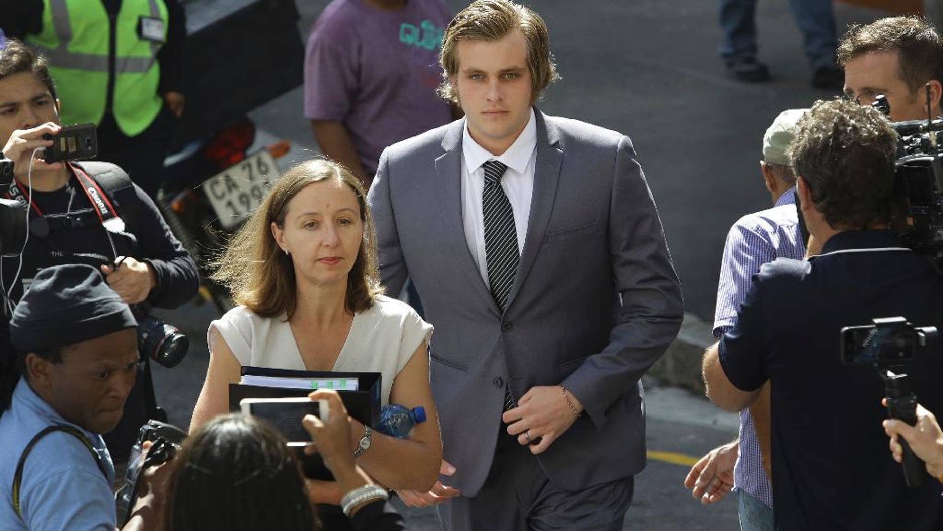 Henri Van Breda, center, accompanied by attorney Lorinda van Niekerk, front, arrives at the supreme court in Cape Town, South Africa, Monday, March 27, 2017. A 22-year-old South African man appeared in court Monday on charges of murdering three members of his family with an axe in their luxury home in Cape Town in January 2015. (AP Photo/STR)
