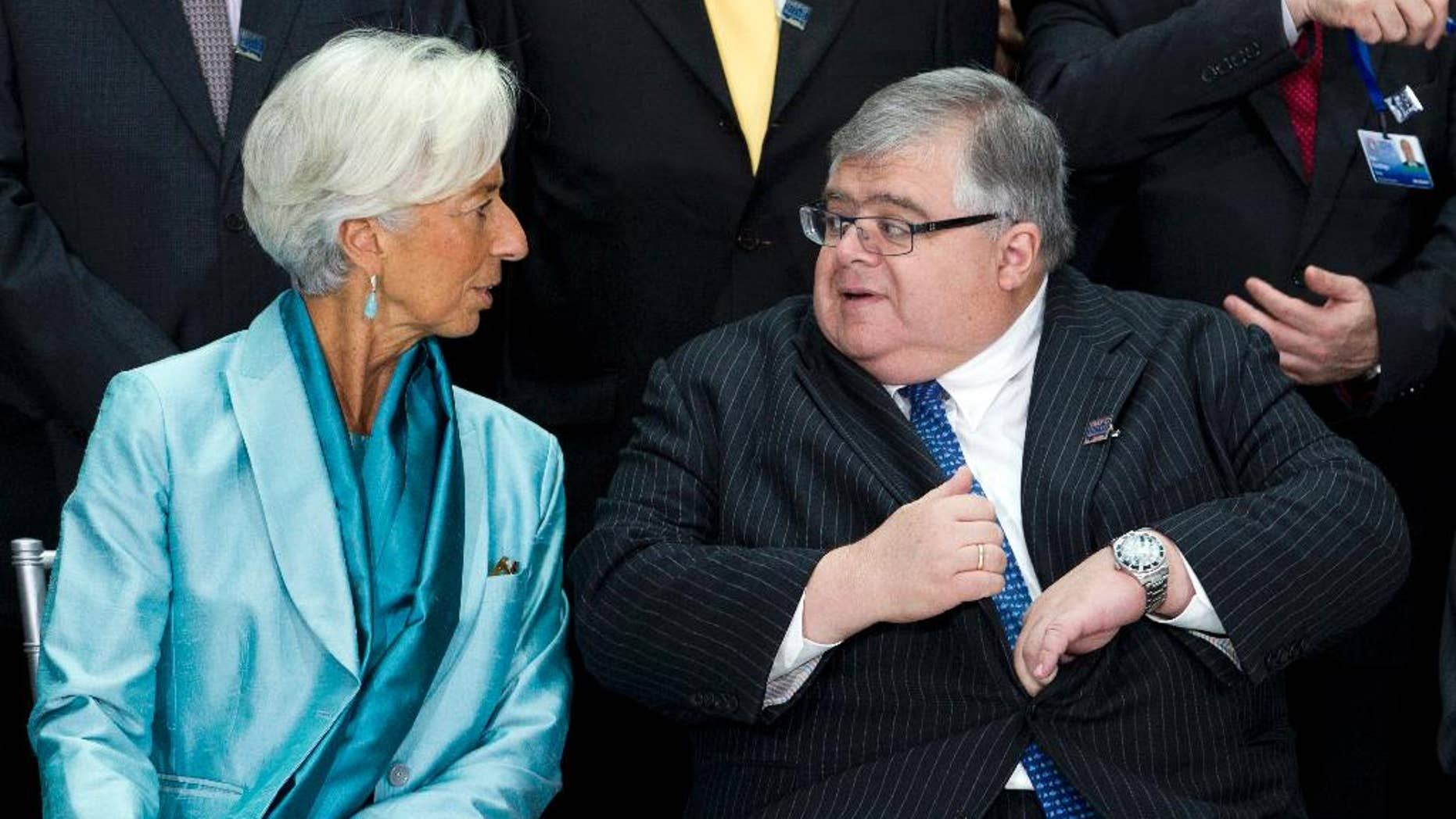 FILE - In this Oct. 8, 2016 file photo, International Monetary and Financial Committee Chair Governor of the Bank of Mexico Agustin Carstens, speaks with International Monetary Fund (IMF) Managing Director Christine Lagarde during the IMF Governors group photo at IMF headquarters in Washington.  Carstens said Thursday, Dec. 1, 2016, he is resigning to become the new general manager of the Bank for International Settlements in Switzerland. ( AP Photo/Jose Luis Magana, File)