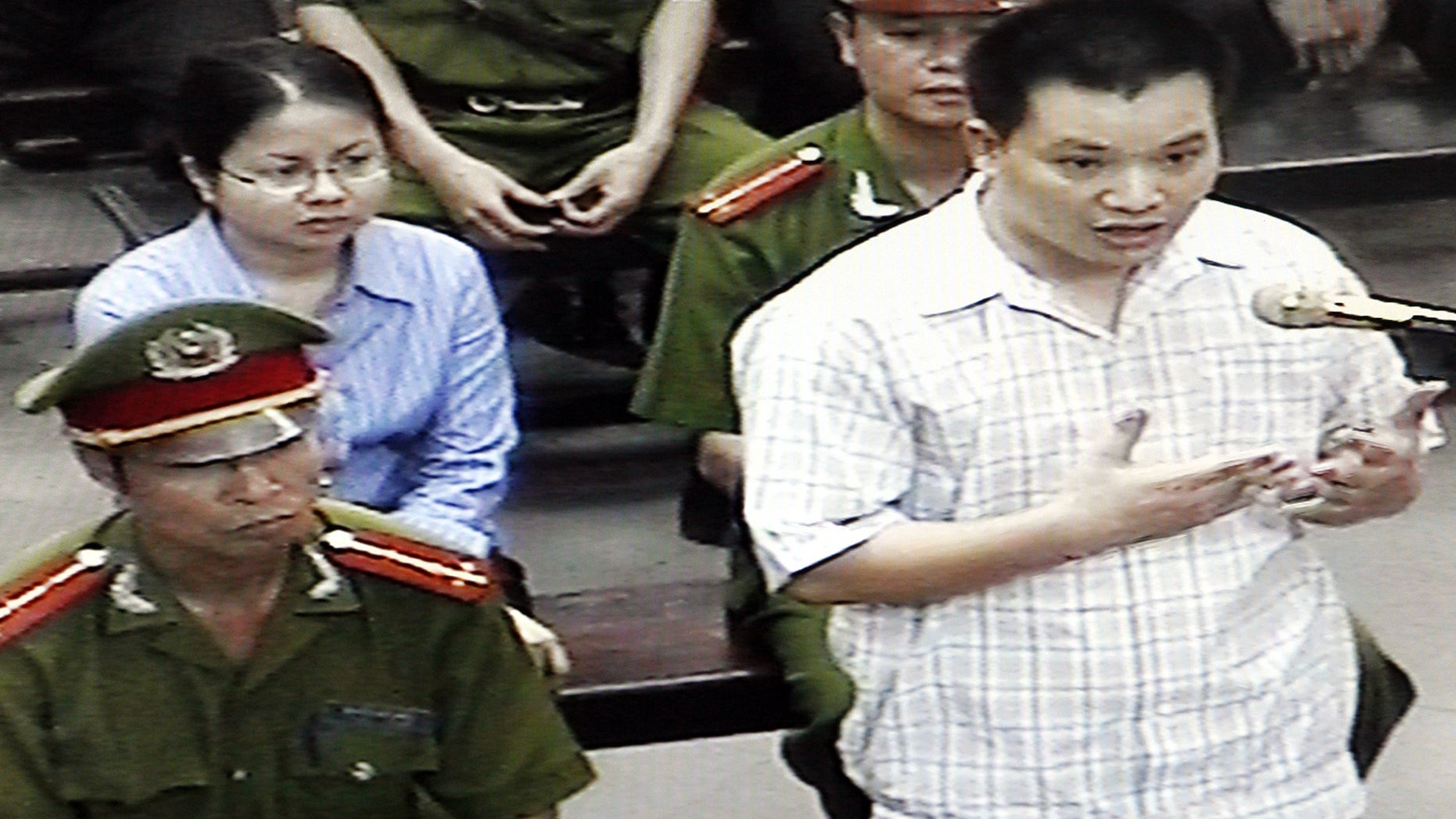 FILE - in this Friday, May 11, 2013 file photo, originally taken from TV footage, Nguyen Van Dai, right, testifies at a court as his fellow human rights activist Le Thi Cong Nhan, left in second row, listens during their trial in Hanoi, Vietnam. Deputy Secretary of State Dan Baer wanted to meet Nguyen Van Dai and Pham Hong Son, two dissidents well known to Western governments and rights organizations when he was in Vietnam. They have each served four-year prison terms in the past. They are under frequent surveillance and are often harassed, yet remain publicly committed to challenging the party, prepared to accept the risks to them and their family in doing so. (AP Photo)