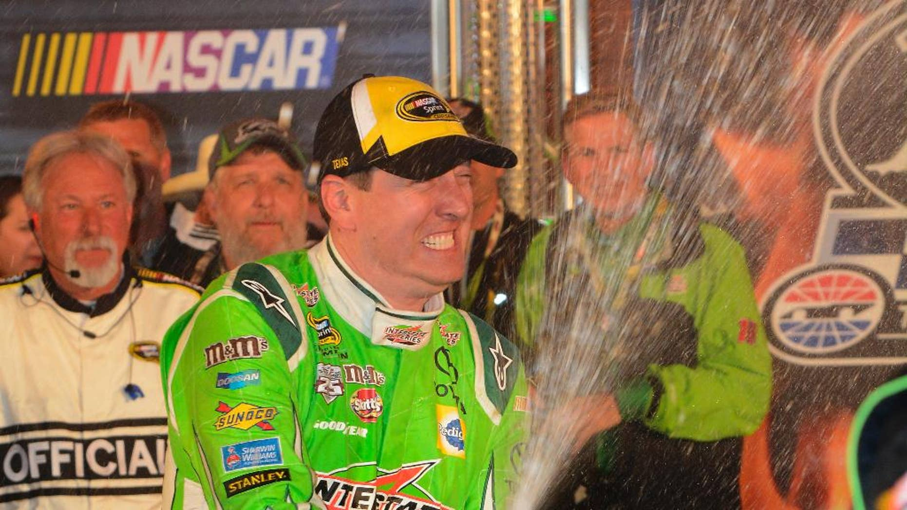 Kyle Busch (18) celebrates winning the NASCAR Sprint Cup Series auto race at Texas Motor Speedway in Fort Worth, Texas, Sunday, April 10, 2016. (AP Photo/Larry Papke)
