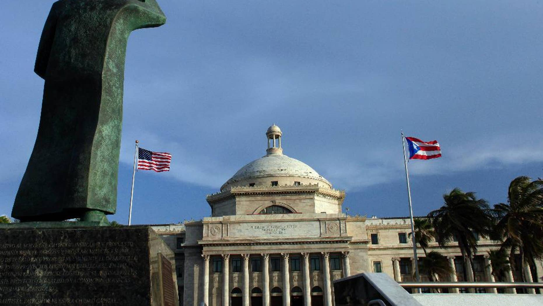 FILE - In this July 29, 2015 file photo, a bronze statue of San Juan Bautista stands in front of Puerto Rico's capitol flanked by U.S. and Puerto Rican flags, in San Juan. A federal control board on Friday, Sept. 30, 2016, took over Puerto Rico's finances and several government agencies for the first time in the U.S. territory's history in a bid to haul the island out of an acute economic crisis.  (AP Photo/Ricardo Arduengo, File)