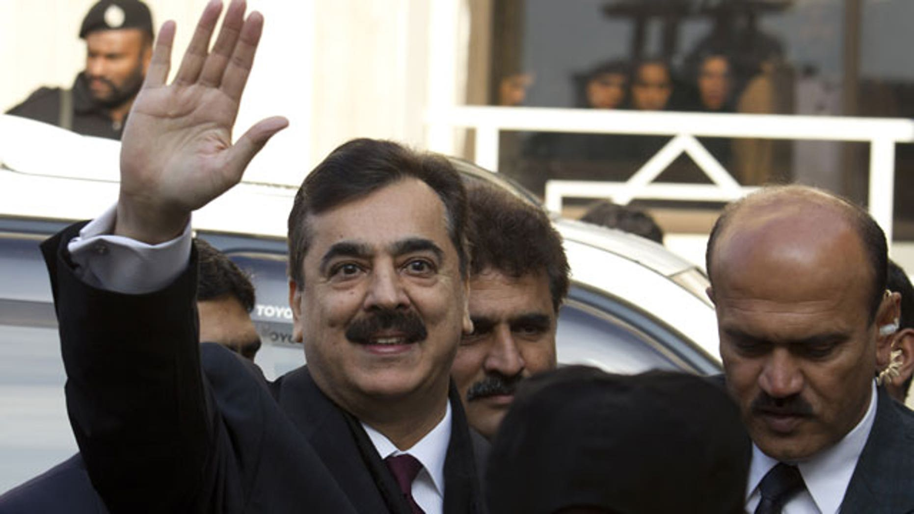 January 19, 2012: Pakistani Prime Minister Yousuf Raza Gilani waves upon his arrival at the Supreme Court in Islamabad.