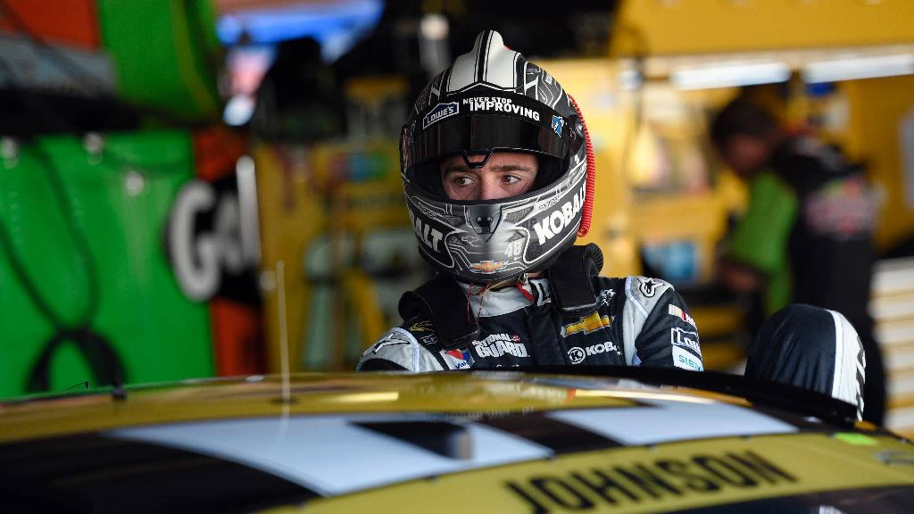 Driver Jimmie Johnson climbs into his car before practice for the NASCAR Sprint Cup series auto race, Friday, Sept. 26, 2014, at Dover International Speedway in Dover, Del. (AP Photo/Nick Wass)