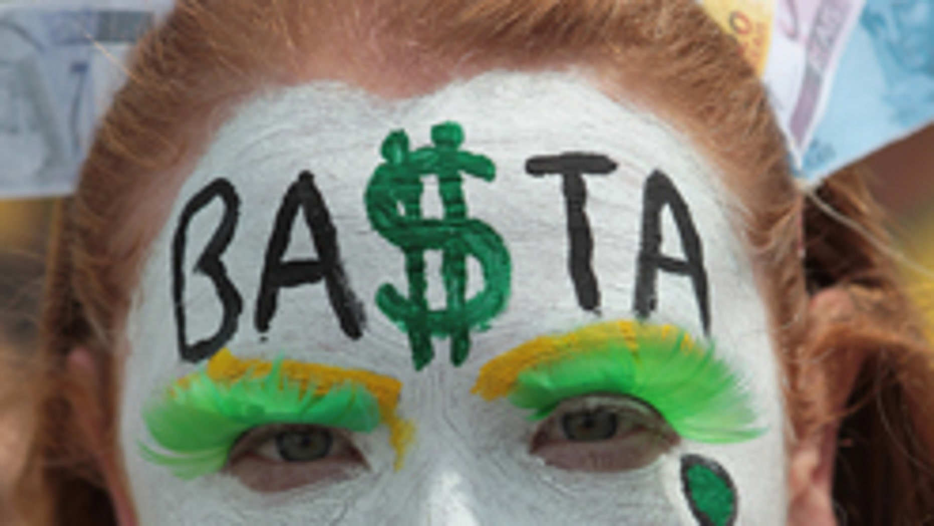 """A demonstrator shouts slogans with """"Suffice"""", written written in Portuguese on her painted face, during protest against the government of Brazil's President Dilma Rousseff, in Brasilia, Brazil, Sunday, March 15, 2015. Protests have been called for across Brazil to demonstrate against President Dilma Rousseff, whose popularity has never been lower as she faces a sputtering economy and a massive corruption scandal. (AP Photo/Eraldo Peres)"""