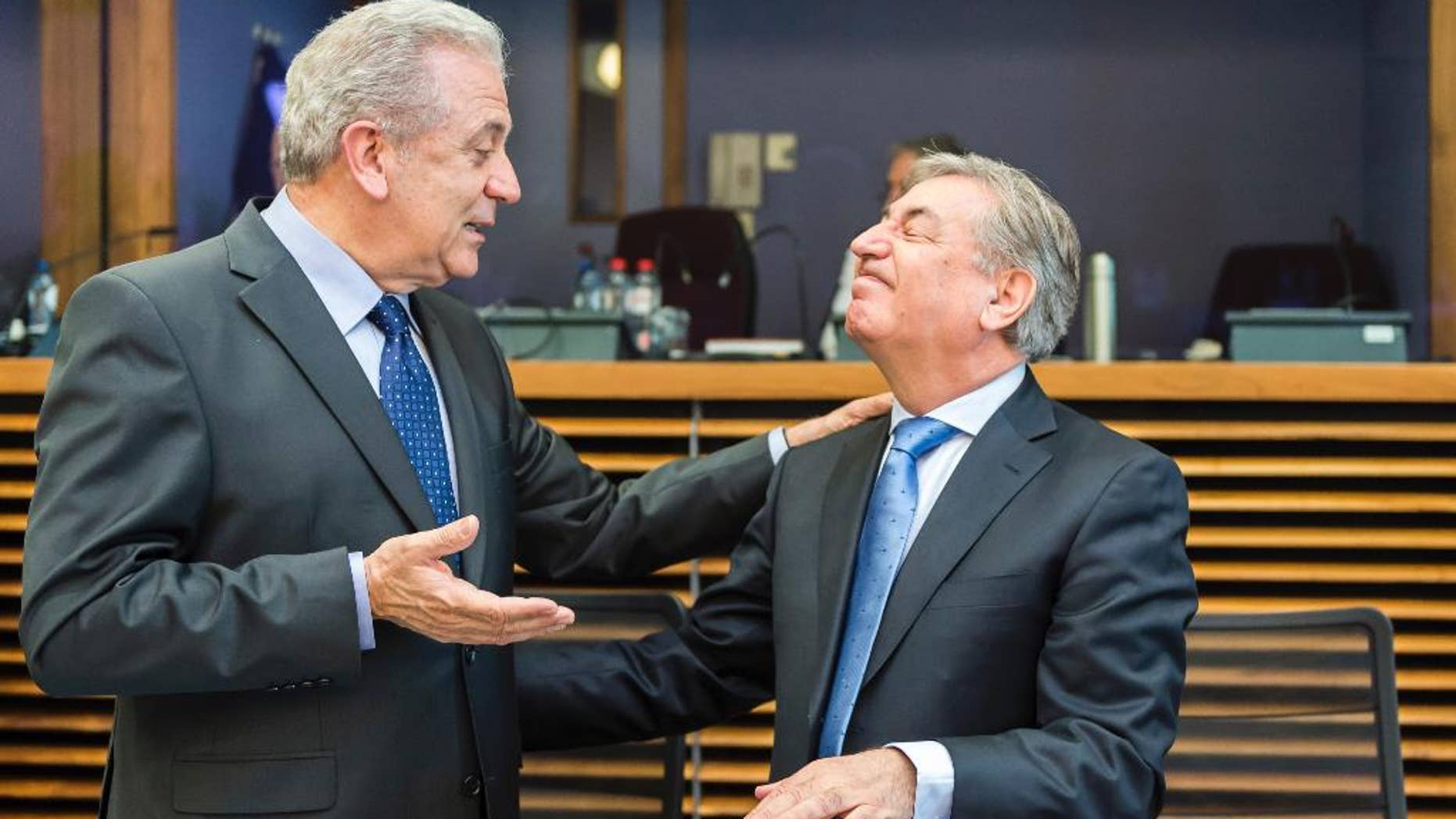 European Commissioner for Migration, Home Affairs and Citizenship Dimitris Avramopoulos, left, talks with European Commissioner for Environment, Maritime Affairs and Fisheries Karmenu Vella during the weekly meeting of commissioners at EU Commission headquarters in Brussels on Wednesday April 20, 2016. (AP Photo/Geert Vanden Wijngaert)