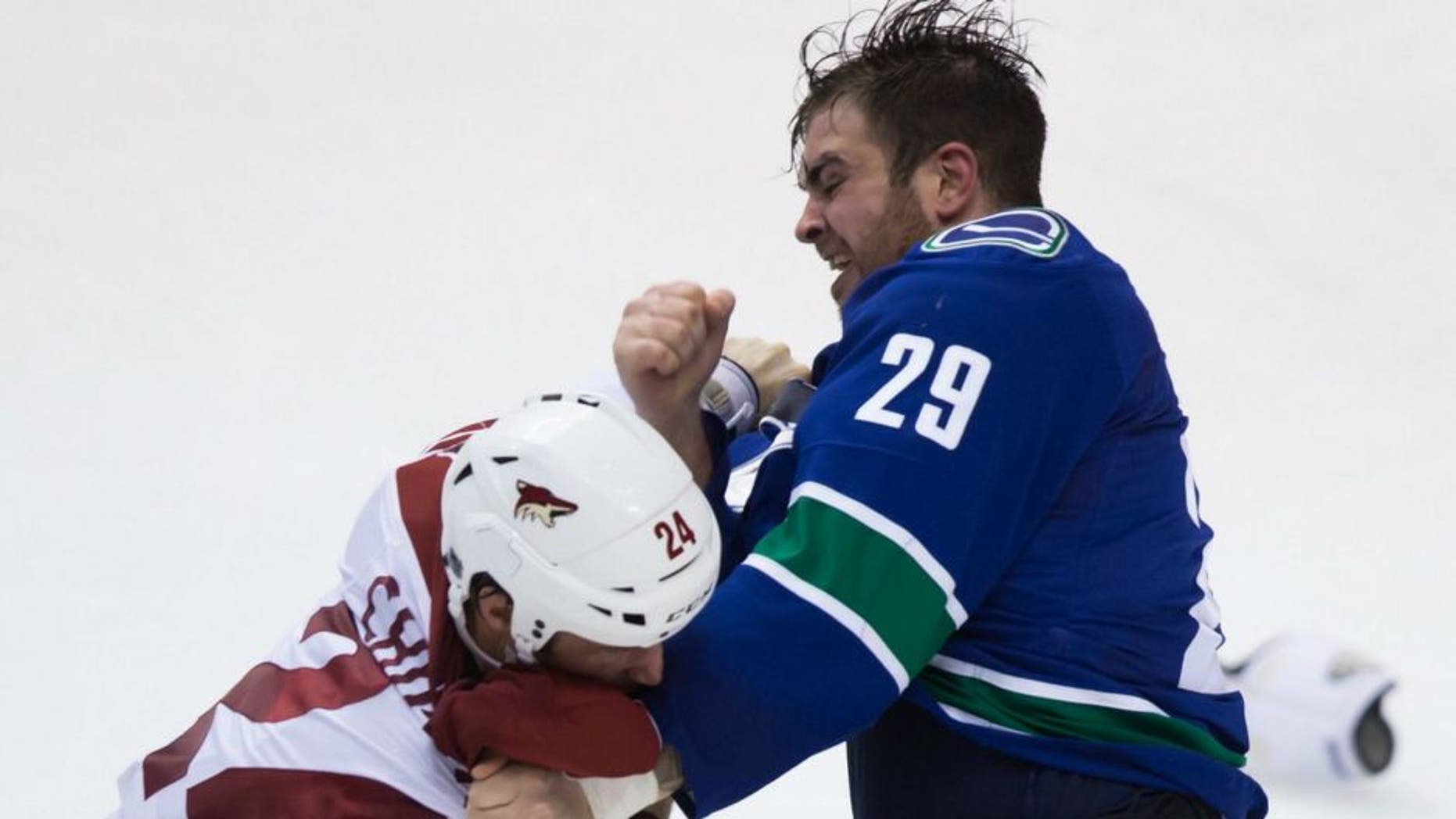 Vancouver Canucks' Tom Sestito, right, and Arizona Coyotes' Kyle Chipchura fight during the second period of an NHL hockey game in Vancouver, British Columbia, Monday, Dec. 22, 2014. (AP Photo/The Canadian Press, Darryl Dyck)
