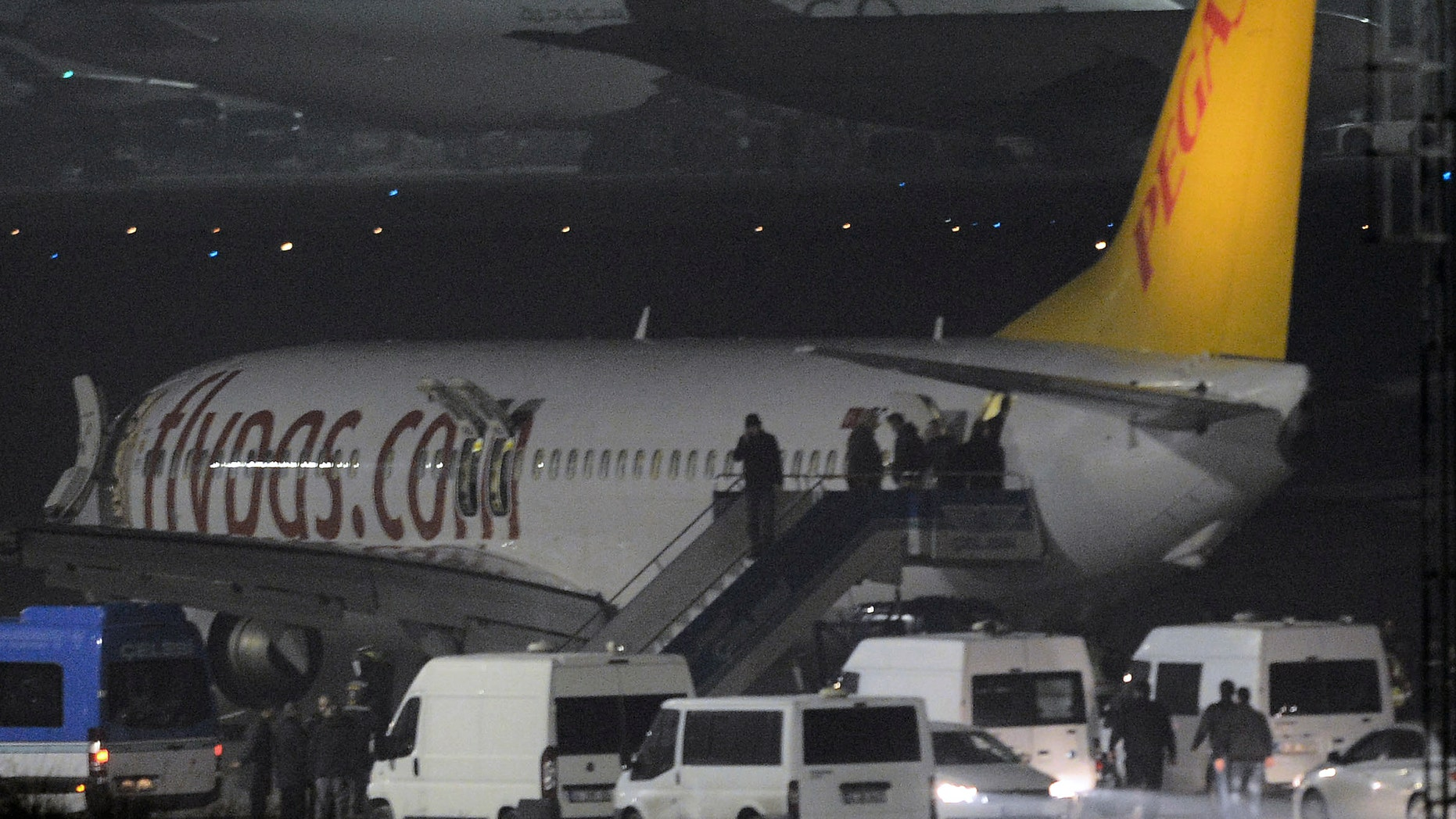 """Passengers of private Turkish company Pegasus leave the plane at the Sabiha Gokcen Airport in Istanbul, Turkey, Friday, Feb. 7, 2014. An official says authorities have subdued a man who attempted to hijack a Turkish plane to Sochi, Russia, and that the other passengers have been evacuated. Huseyin Avni Mutlu, the Istanbul governor, says on Twitter that """"the operation has ended."""" In another tweet Friday, he said all passengers were evacuated """"without any problems.""""(AP Photo/Emrah Gurel)"""