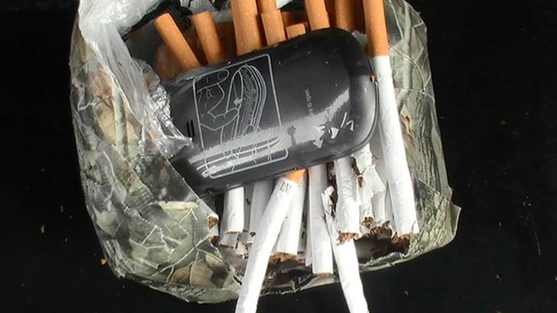 This undated photo mprovided by the Florida Department of Corrections shows a cellphone and cigarettes that were found inside a camouflage package, January 25, 2014, near an undisclosed Florida state prison. Prison officials in Florida and nationwide are fighting a different type of contraband being smuggled to inmates: cellphones. They're being hidden in babies' diapers, Ramen Noodle Soup packages, footballs, soda cans and body cavities.Two murderers used cellphones to plan their escape from a Florida prison last year where the state confiscated 11 cellphones per day in its prisons. (AP Photo/Florida Department of Corrections)