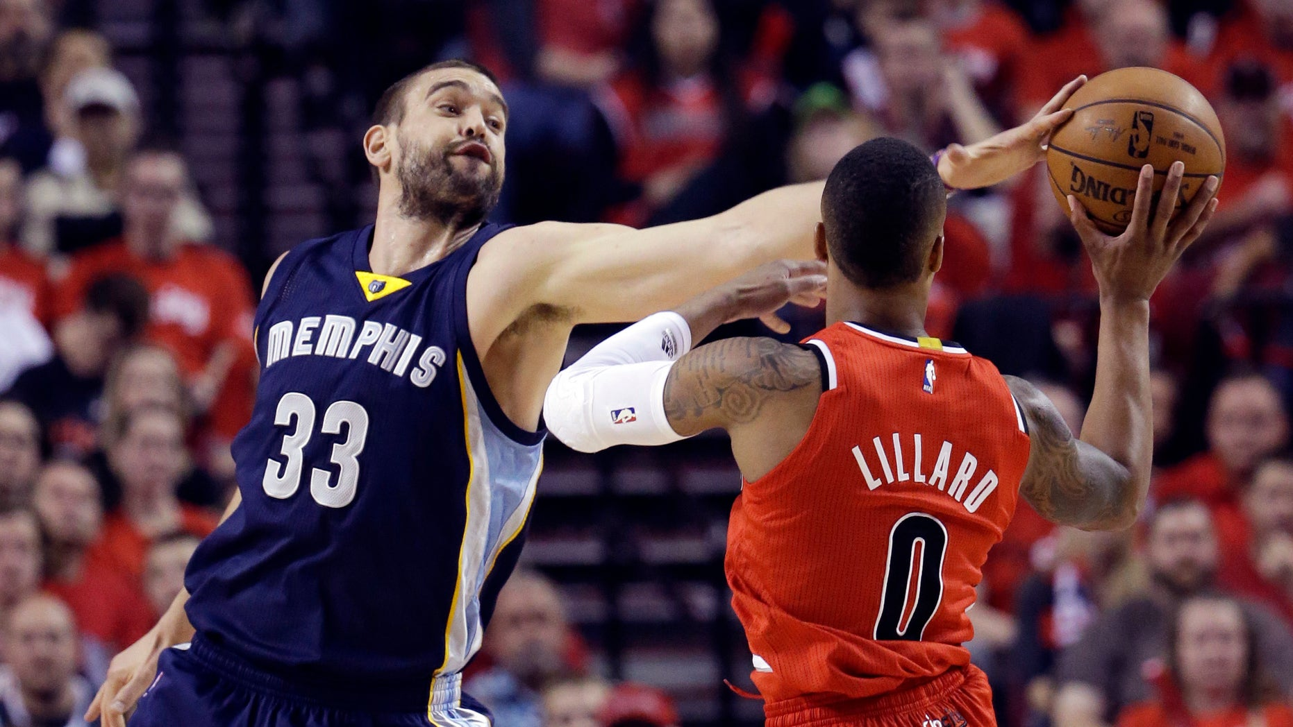 Memphis Grizzlies center Marc Gasol, left, gets a piece of the ball while defending Portland Trail Blazers guard Damian Lillard during the first half of Game 3 of a first-round NBA basketball playoff series in Portland, Ore., Saturday, April 25, 2015. (AP Photo/Don Ryan)