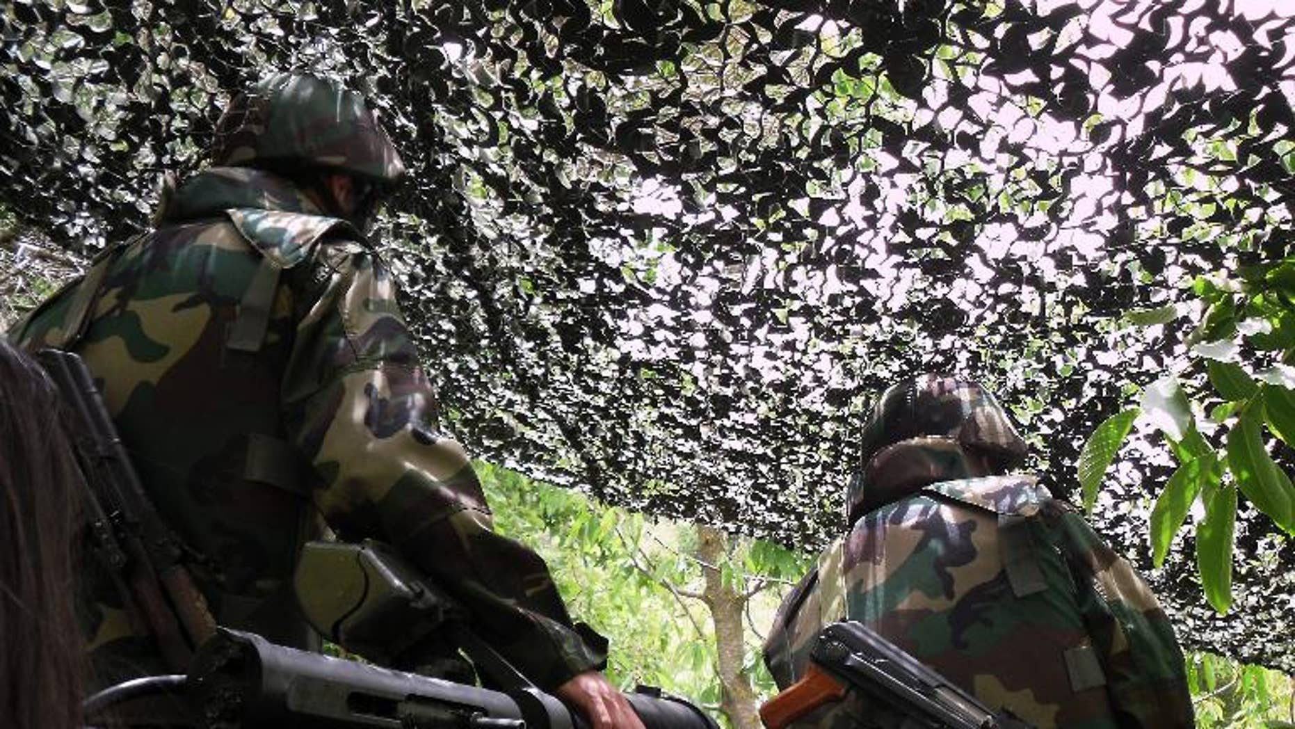 Lebanese Hezbollah militants stand in their post in Iqlim al-Touffah, southern Lebanon on May 16, 2010
