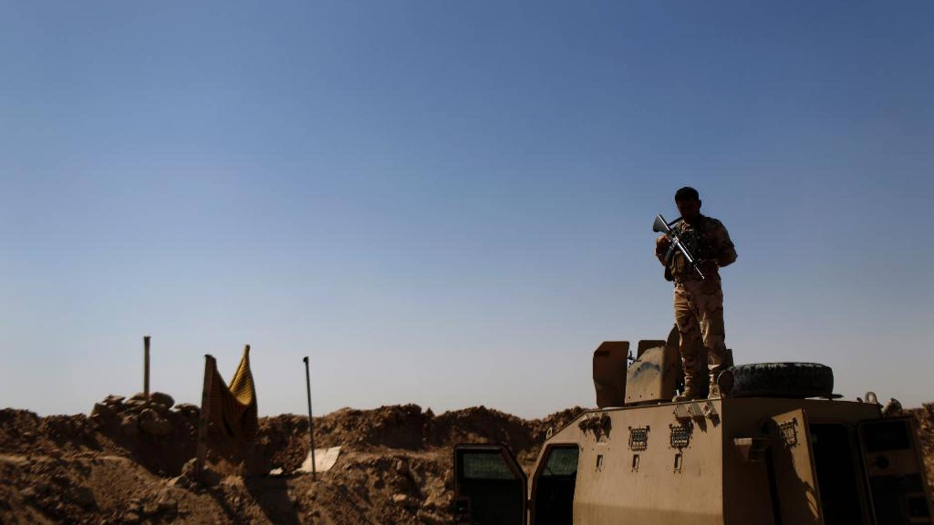 A Kurdish Peshmerga fighter stands guard atop an armored vehicle at a combat outpost on the outskirts of Makhmour, 300 kilometers (186 miles) north of Baghdad, Iraq, Saturday, Sept. 6, 2014. The U.S. and nine key allies agreed Friday, that the Islamic State group is a significant threat to NATO countries and that they will take on the militants by squeezing their financial resources and going after them with military might. (AP Photo/ Marko Drobnjakovic)