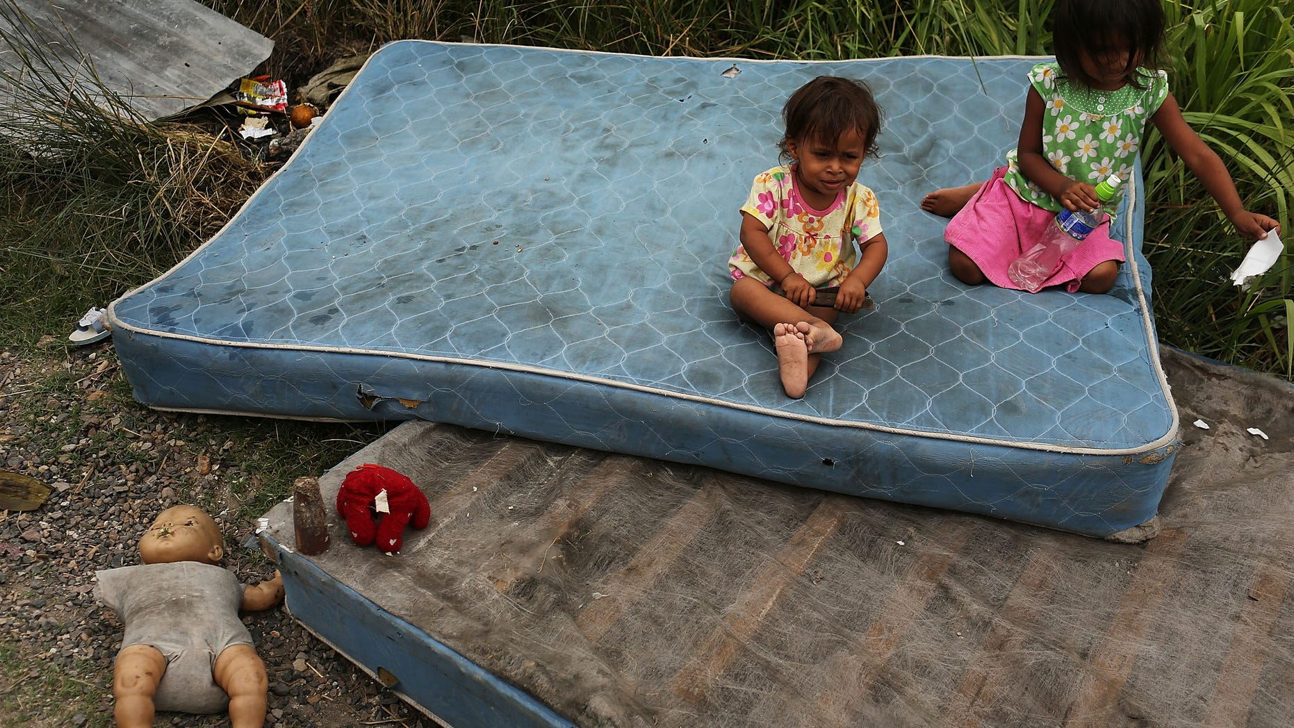 TEGUCIGALPA, HONDURAS - JULY 20:  Children sit on mattresses as their home and neighborhood are forcefully dismantled in a shanty town after the government claimed that the settlement was illegal on July 20, 2012 in Tegucigalpa, Honduras. Land disputes are becoming increasingly frequent in Honduras  which is alarming the nation's business class while sowing fears of increased political violence. In a nation where 72% of the poorest landowners hold only 11.6% of cultivated land, tensions are rising as the poor have few places to go and little opportunities for productive employment. Honduras now has the highest per capita murder rate in the world and its capital city, Tegucigalpa, is plagued by violence, poverty, homelessness and sexual assaults. With an estimated 80% of the cocaine entering the United States now being trans-shipped through Honduras, the violence on the streets is a spillover from the ramped rise in narco-trafficking.  (Photo by Spencer Platt/Getty Images)
