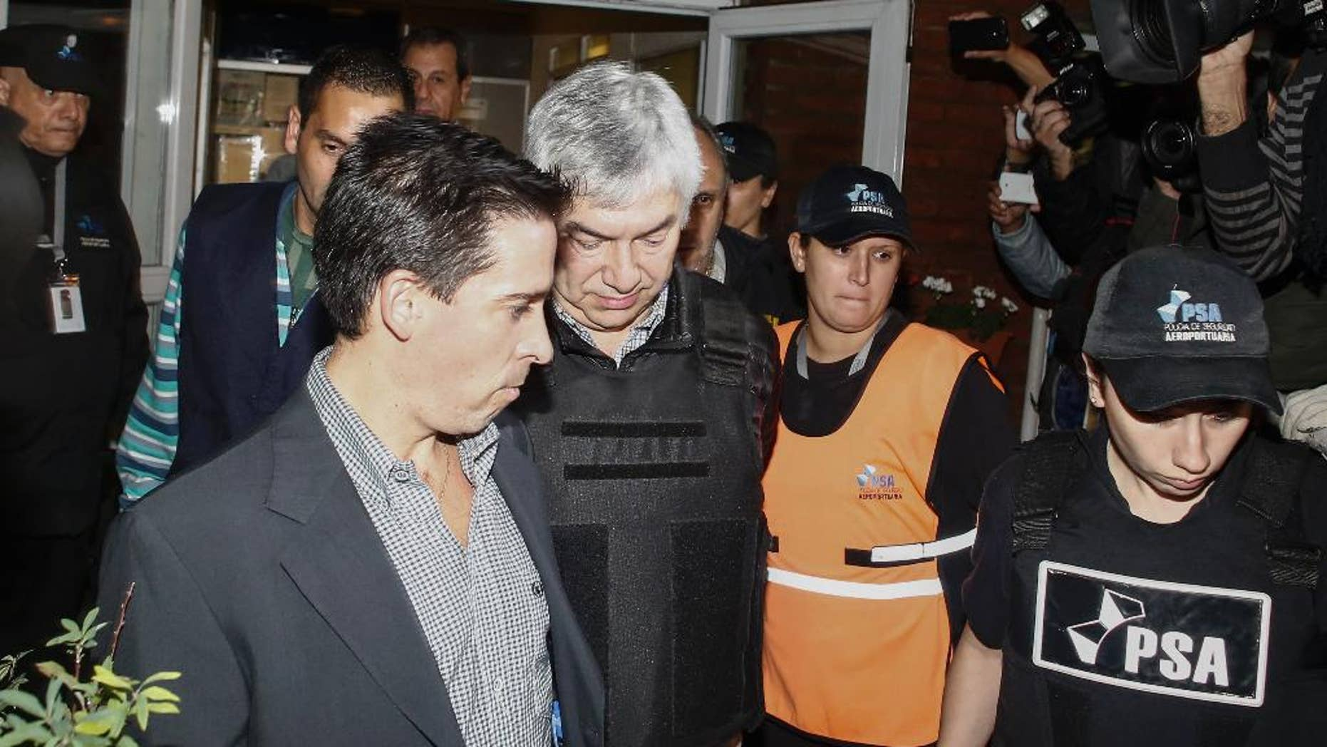 Argentine businessman Lazaro Baez, center, is escorted by police after being arrested as part of an investigation into alleged money laundering, at an airport on the outskirts of Buenos Aires, Argentina, late Tuesday, April 5, 2016. Baez, who got large public works contracts during the Kirchner and Fernandez administrations, is accused of embezzling and laundering millions. He denies any wrongdoing. (AP Photo/Agustin Marcarian)