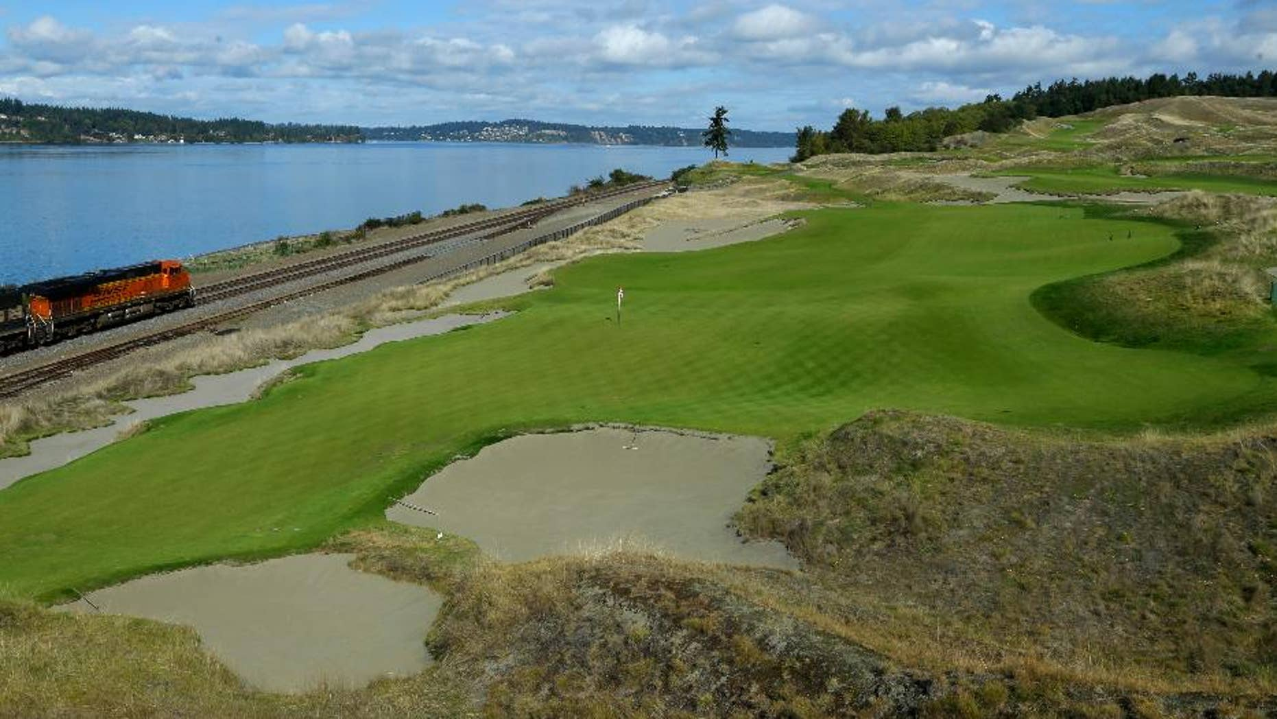 In this Sept. 30, 2014, file photo, the 16th hole of the Chambers Bay golf course is shown as a freight train passes at left in University Place, Wash. Next week the course, which opened in 2007, will become the youngest golf course to host the U.S. Open since Hazeltine in 1970. (AP Photo/Ted S. Warren, file)